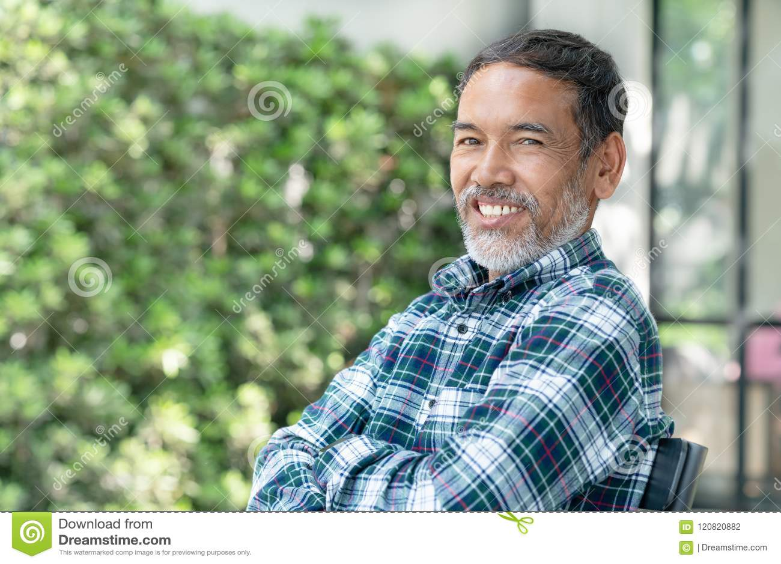 Portreta uśmiechnięty atrakcyjny dojrzały azjatykci mężczyzna przechodzić na emeryturę z elegancki krótki brody siedzieć plenerow