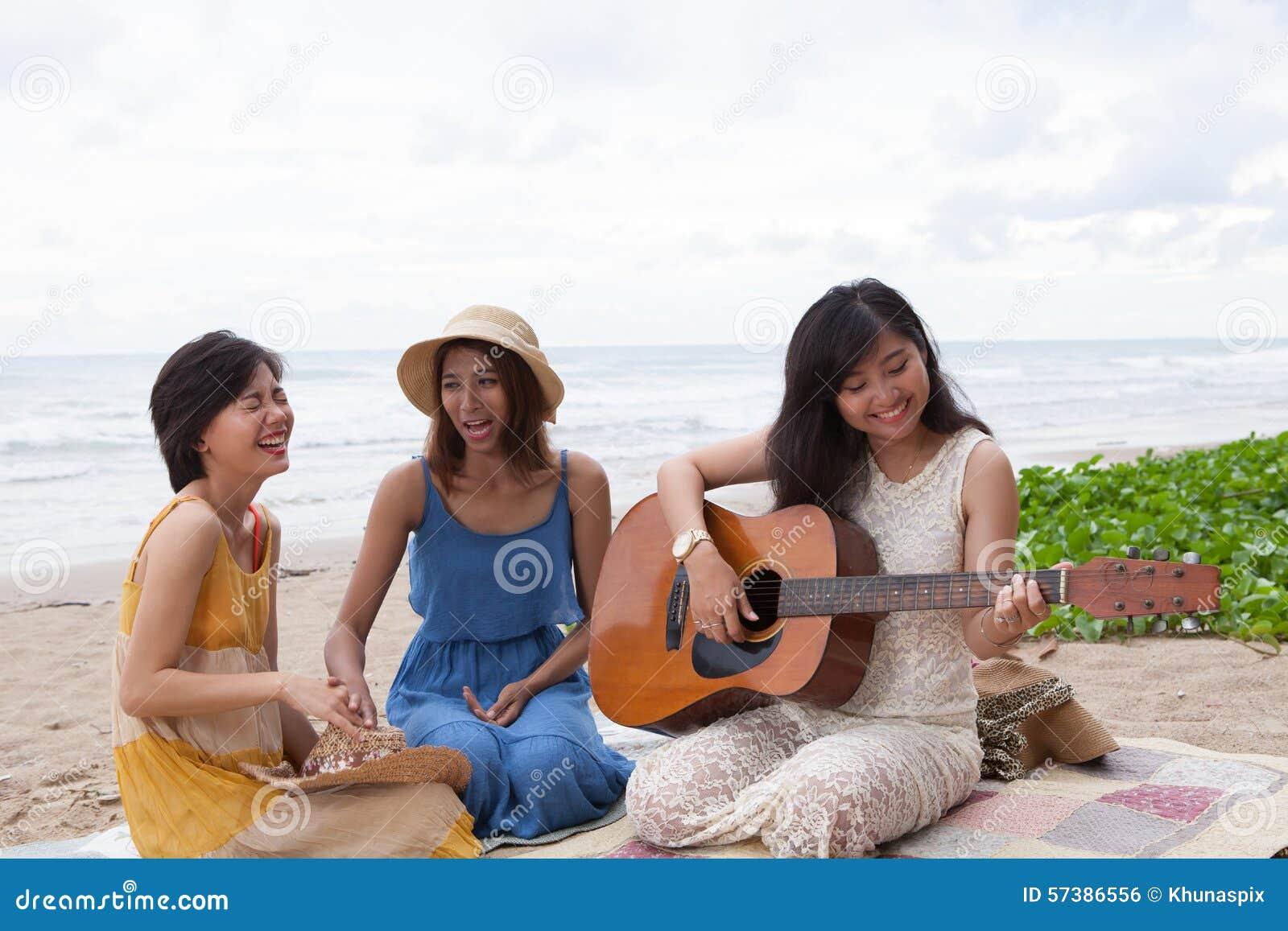 Portretgroep jonge Aziatische vrouw het spelen gitaar in overzees strand