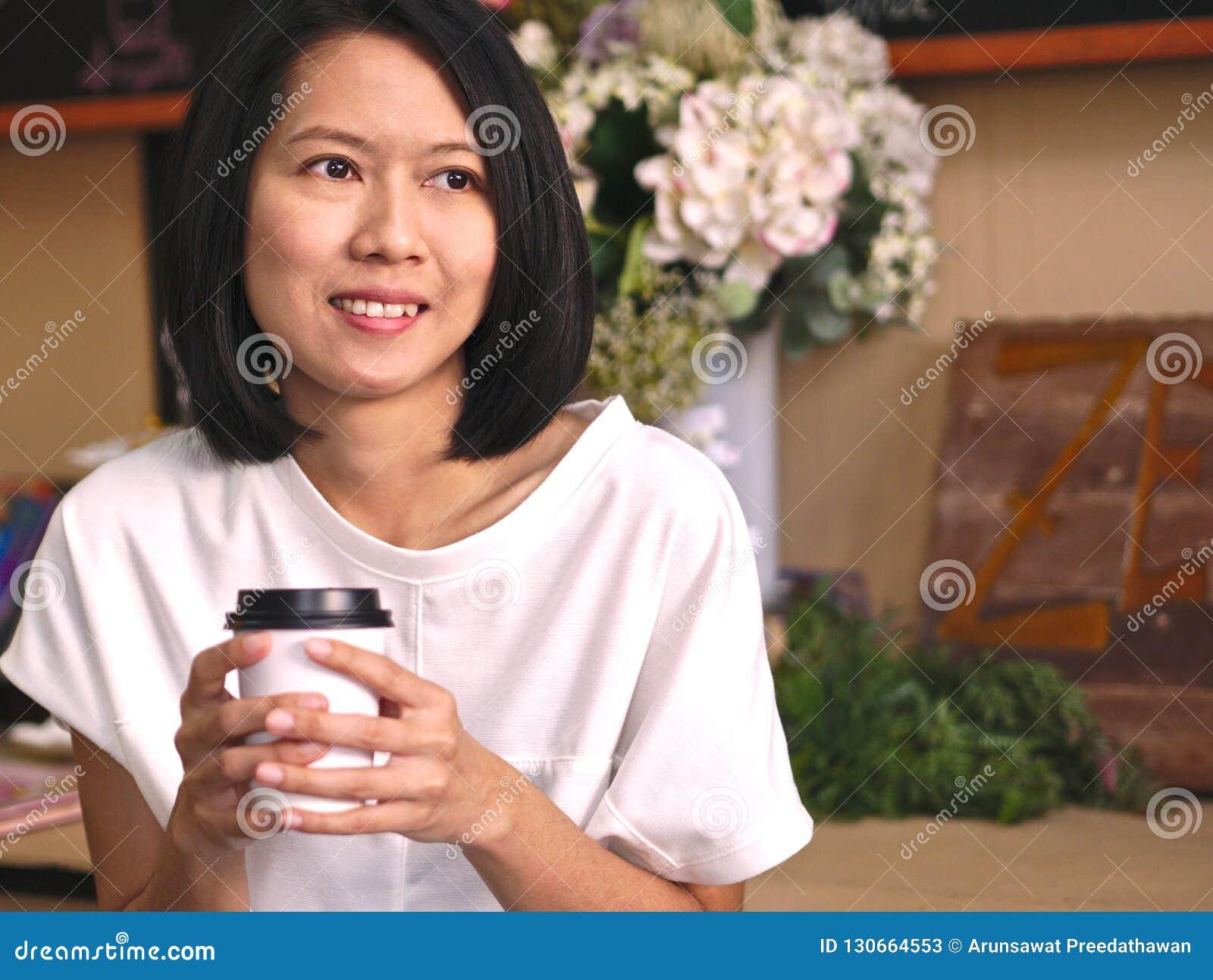Portretten die van Aziatische vrouw een kop van koffie houden door twee handen die aan haar linkerhand in comfortabele koffiewink
