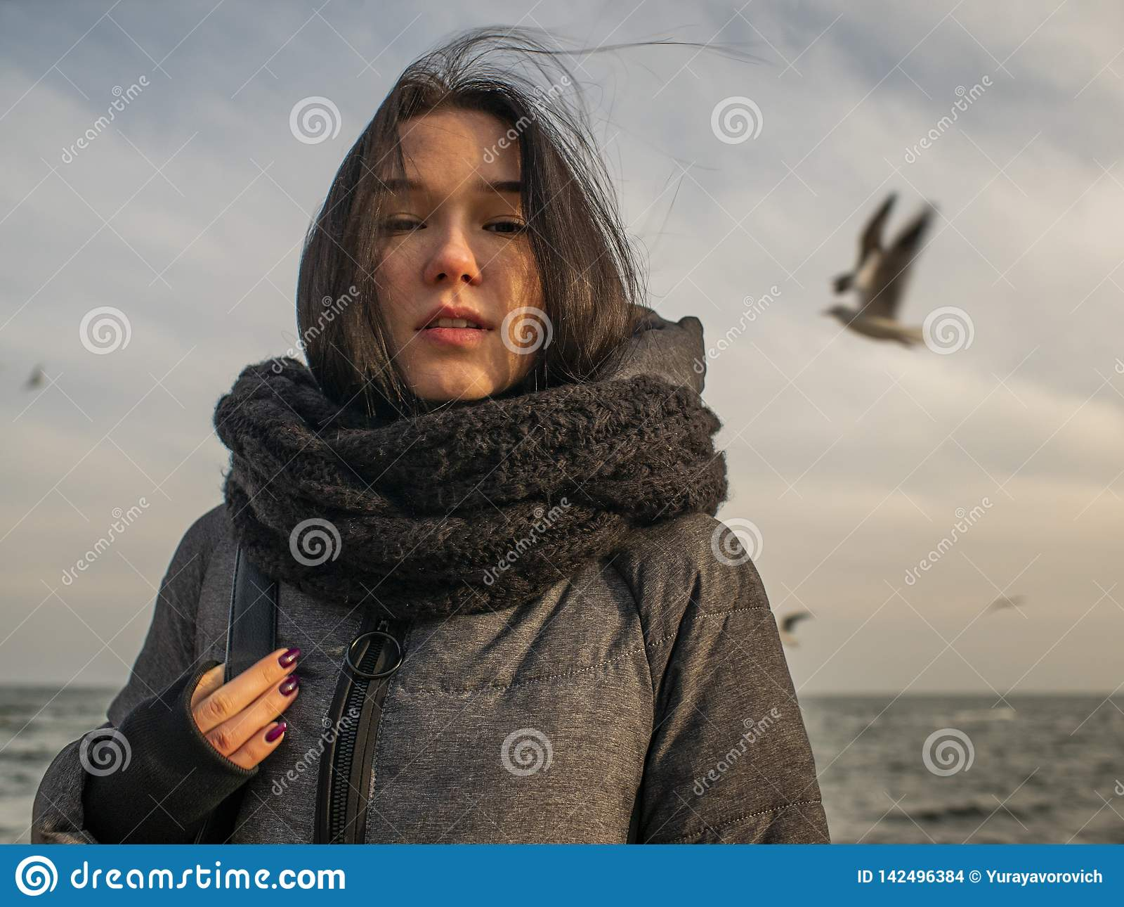 Portretten jong aantrekkelijk meisje op de achtergrond van het overzees, de hemel en de meeuwen
