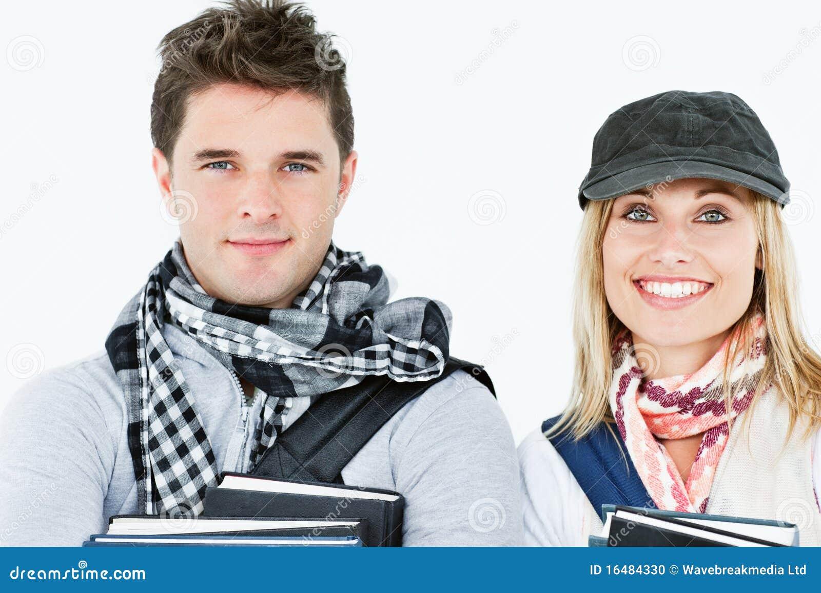 Portretten van twee glimlachende studenten die boeken houden