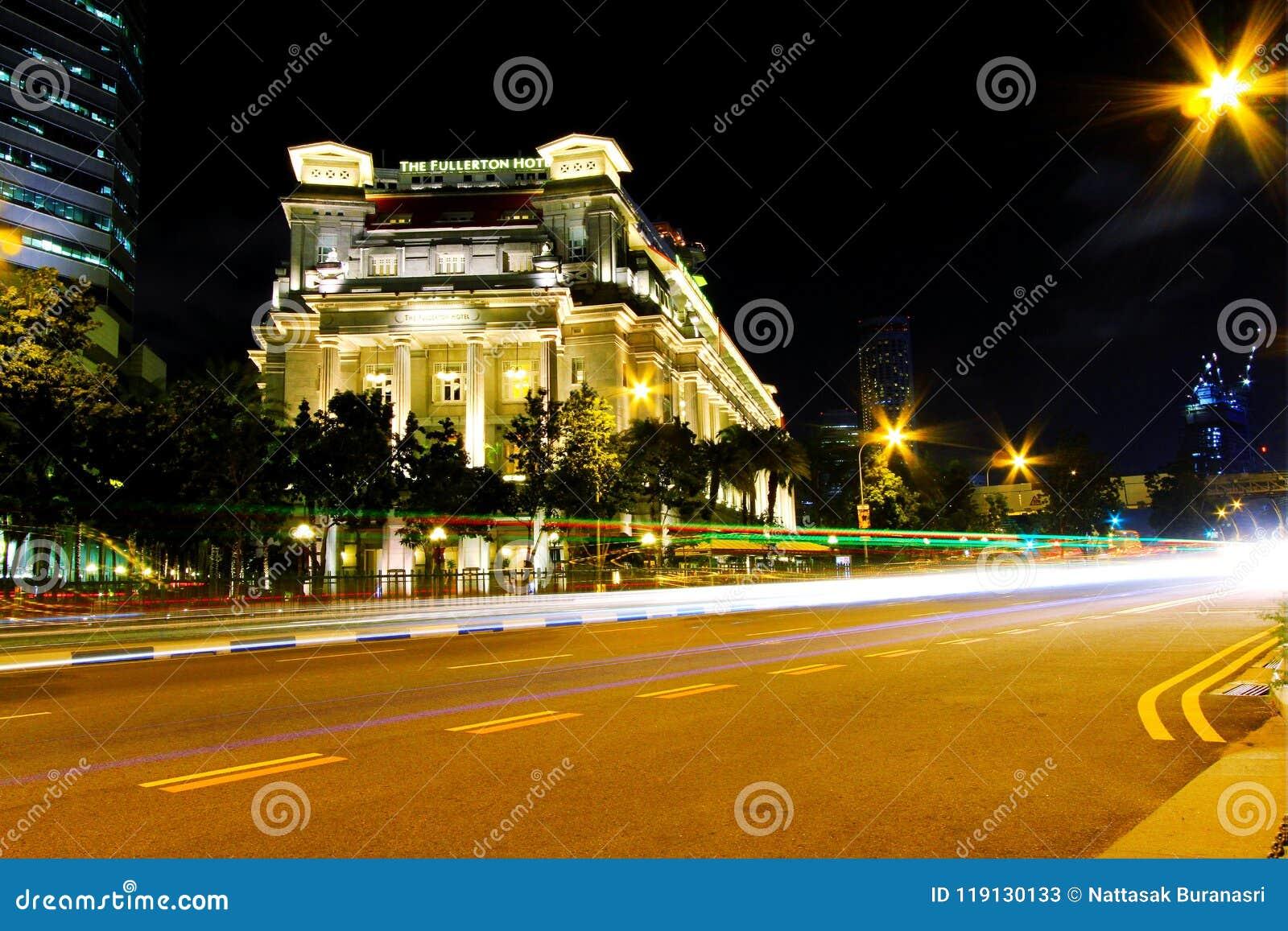 Poruszający światła ruchu ogony transport przy nocą z Fullerton hotelowym tłem przy Singapur