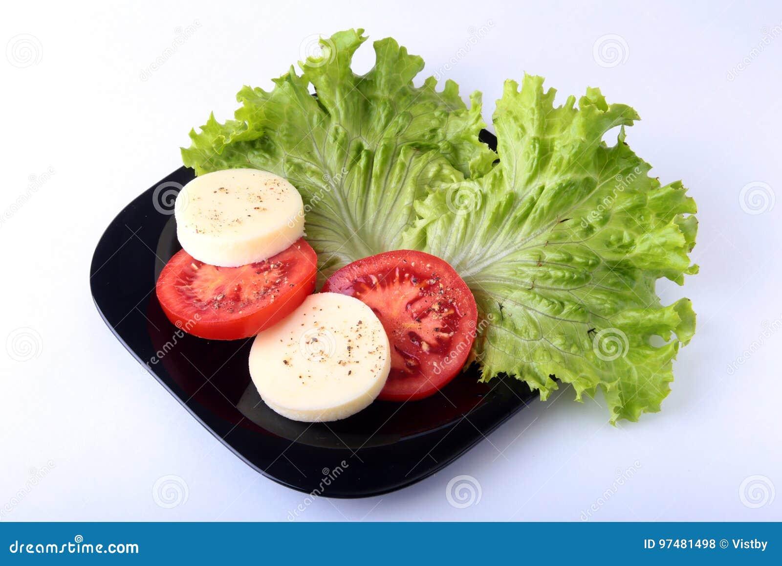 Porzione di mozzarella con i pomodori, la foglia della lattuga ed il condimento balsamico sulla banda nera colpo del primo piano