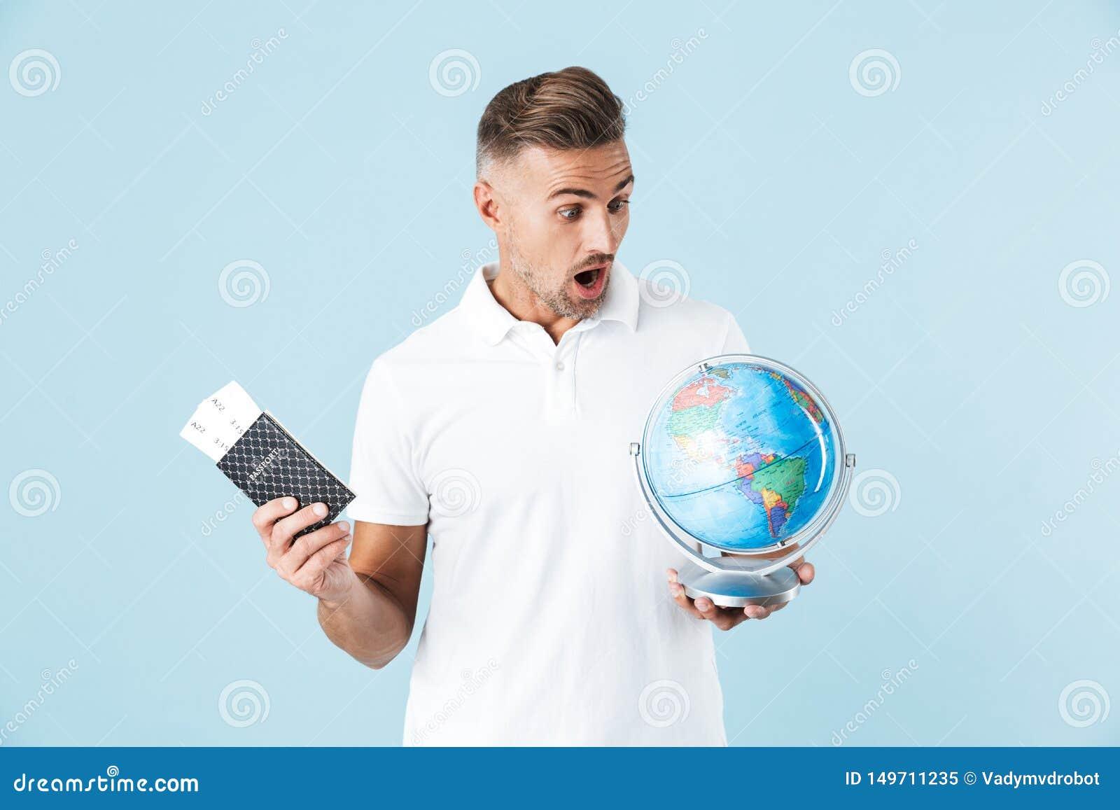 Posa adulta colpita emozionante bella dell uomo isolata sopra il passaporto blu della tenuta del fondo della parete con i bigliet