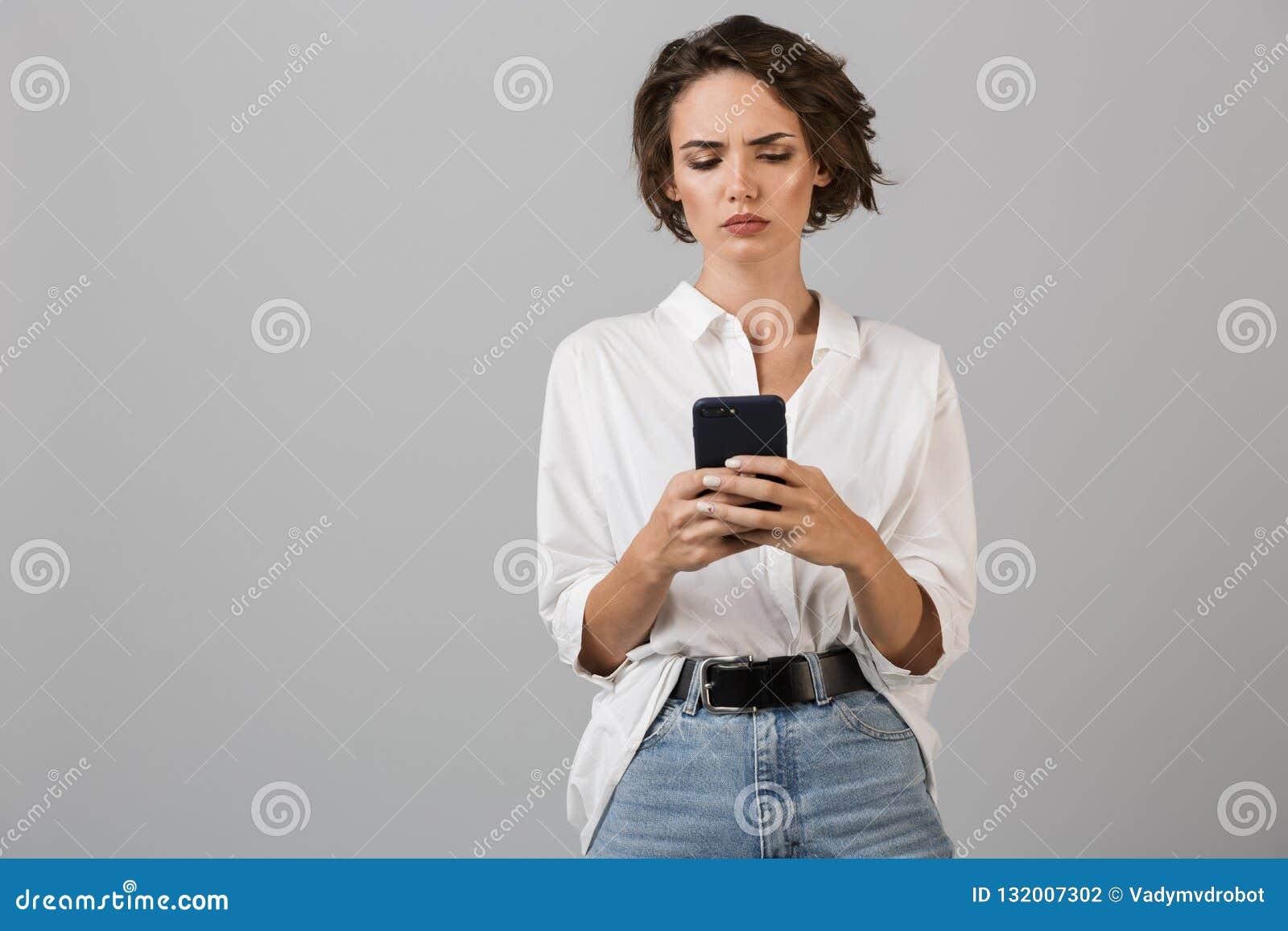 Posa giovane confusa di pensiero della donna di affari isolata sopra il fondo grigio della parete facendo uso della chiacchierata