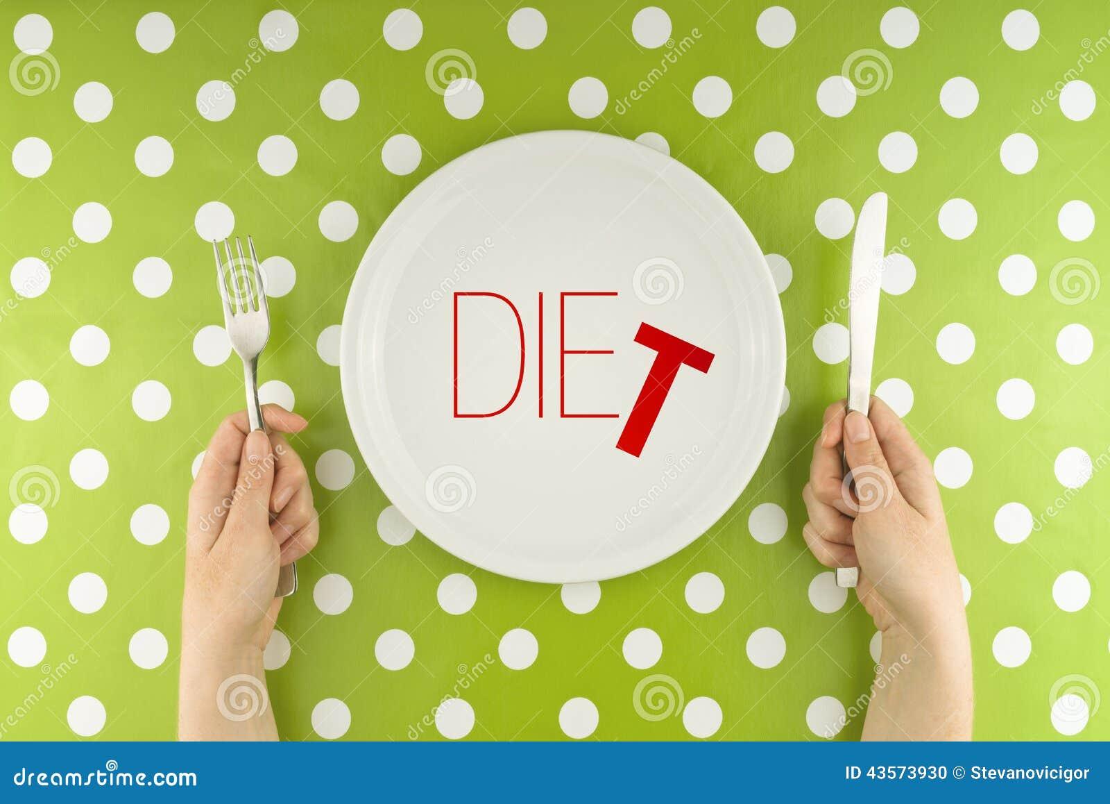 Posate della tenuta delle mani sopra il piatto stante a dieta