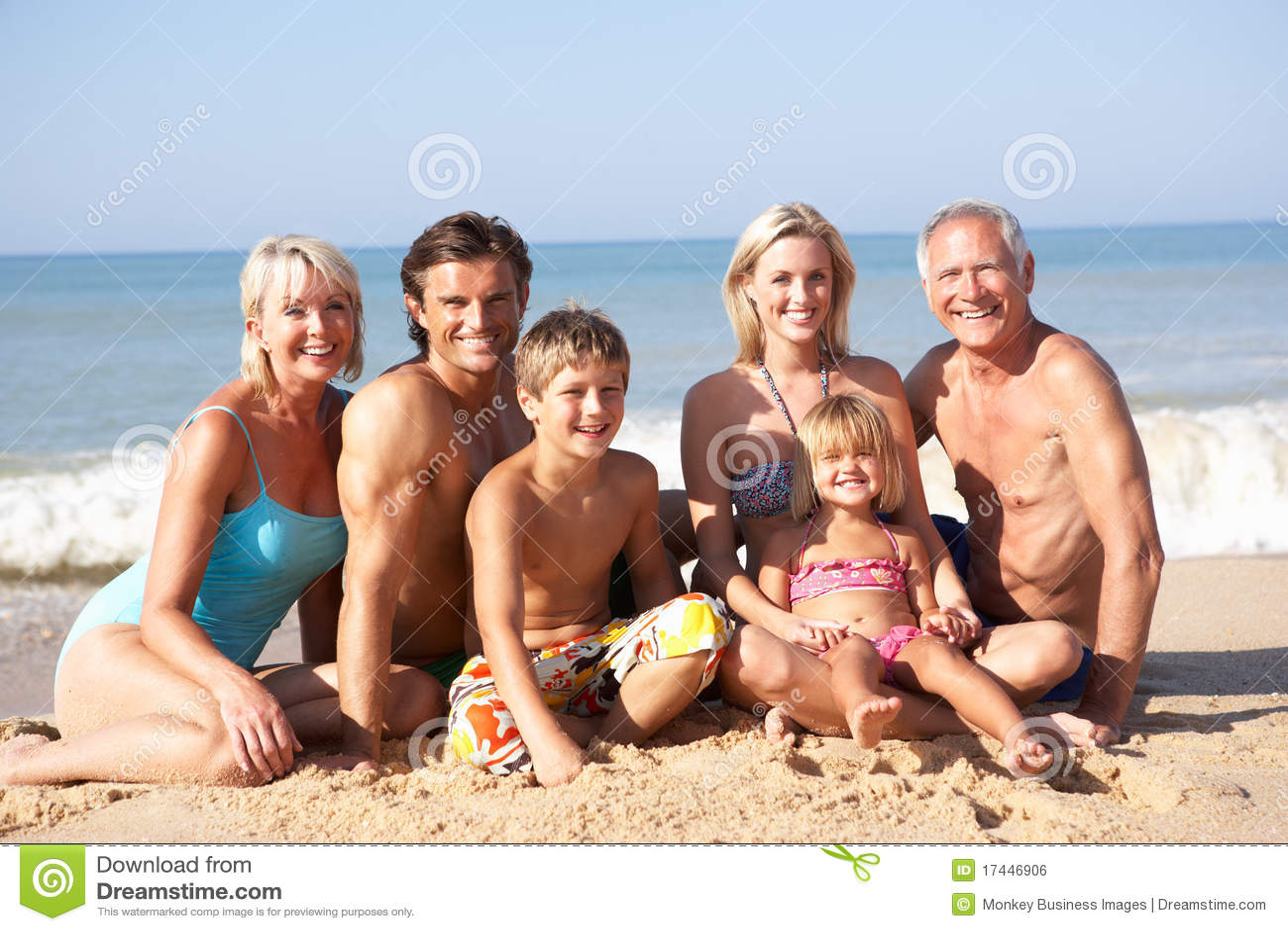 Pose da família de três gerações na praia