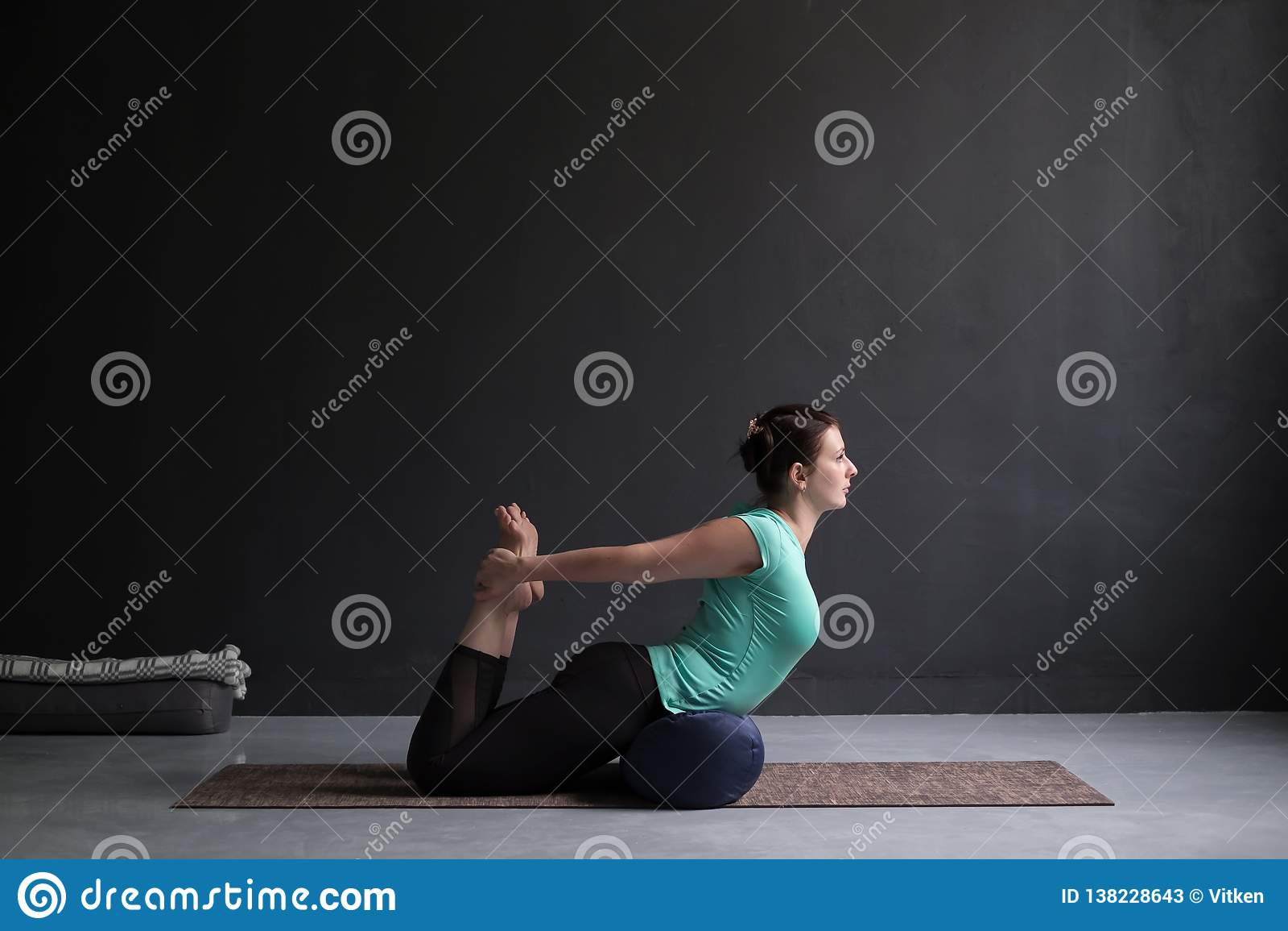 Pose de pratique d arc de yoga de femme, Dhanurasana utilisant le traversin