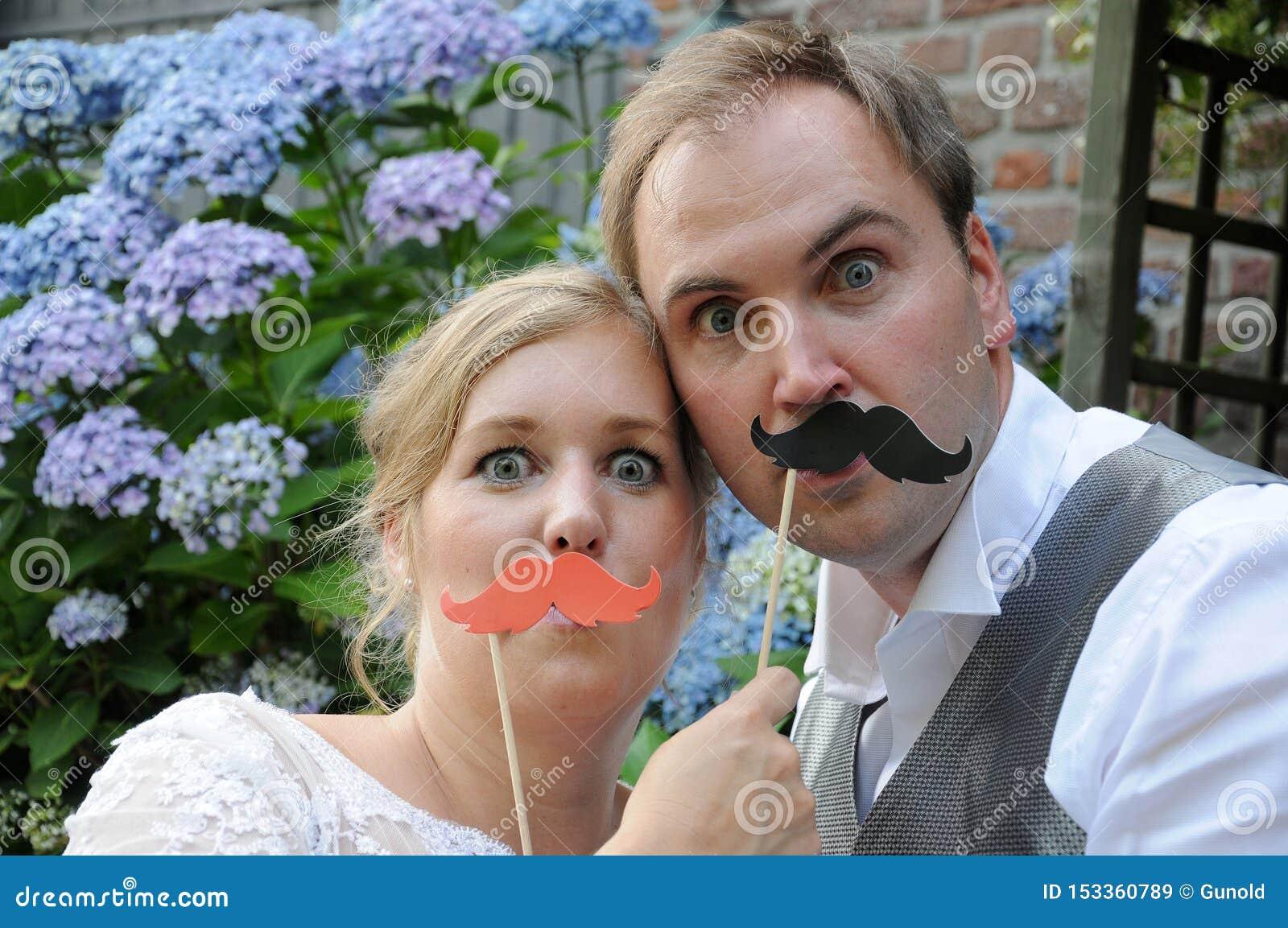 Pose dos noivos giggly na frente de uma foto-cabine