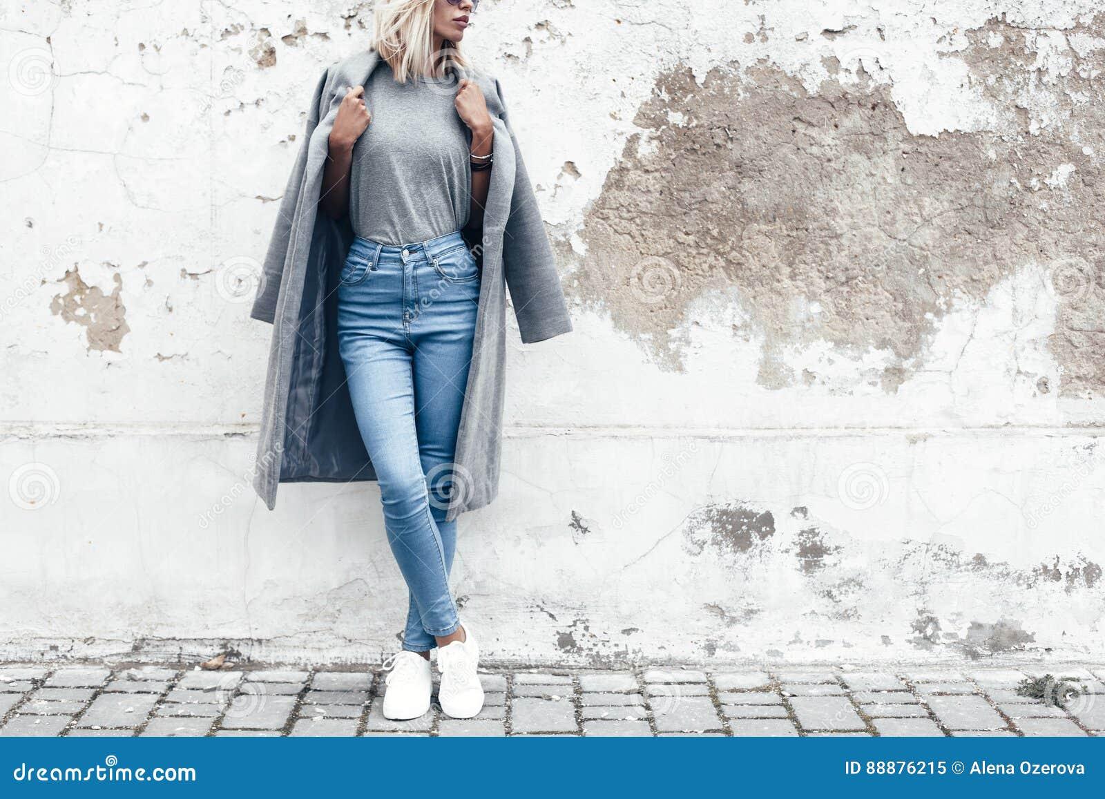 Pose modèle dans le T-shirt simple contre le mur de rue