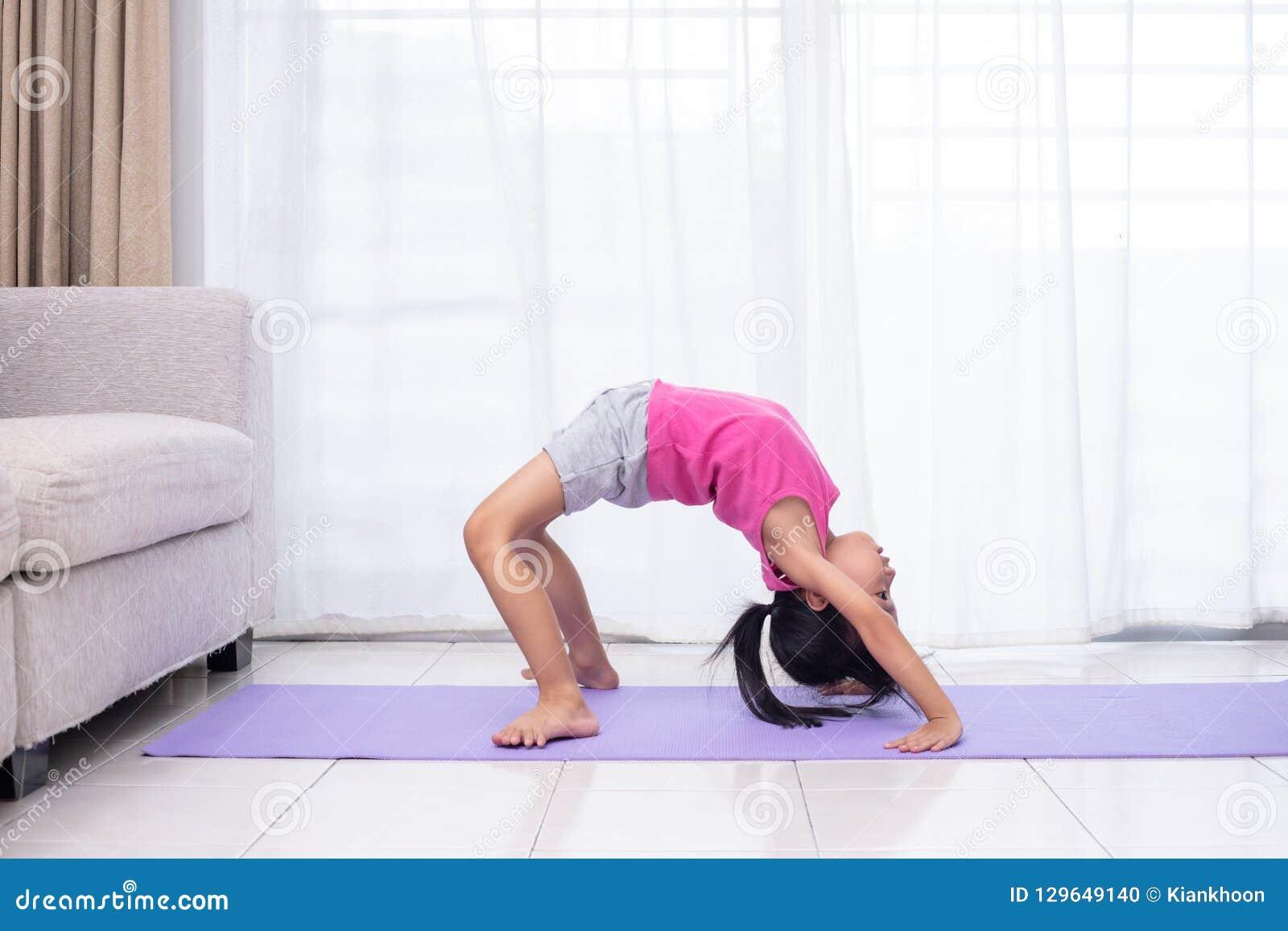 Pose praticando da ioga da menina chinesa asiática em uma esteira
