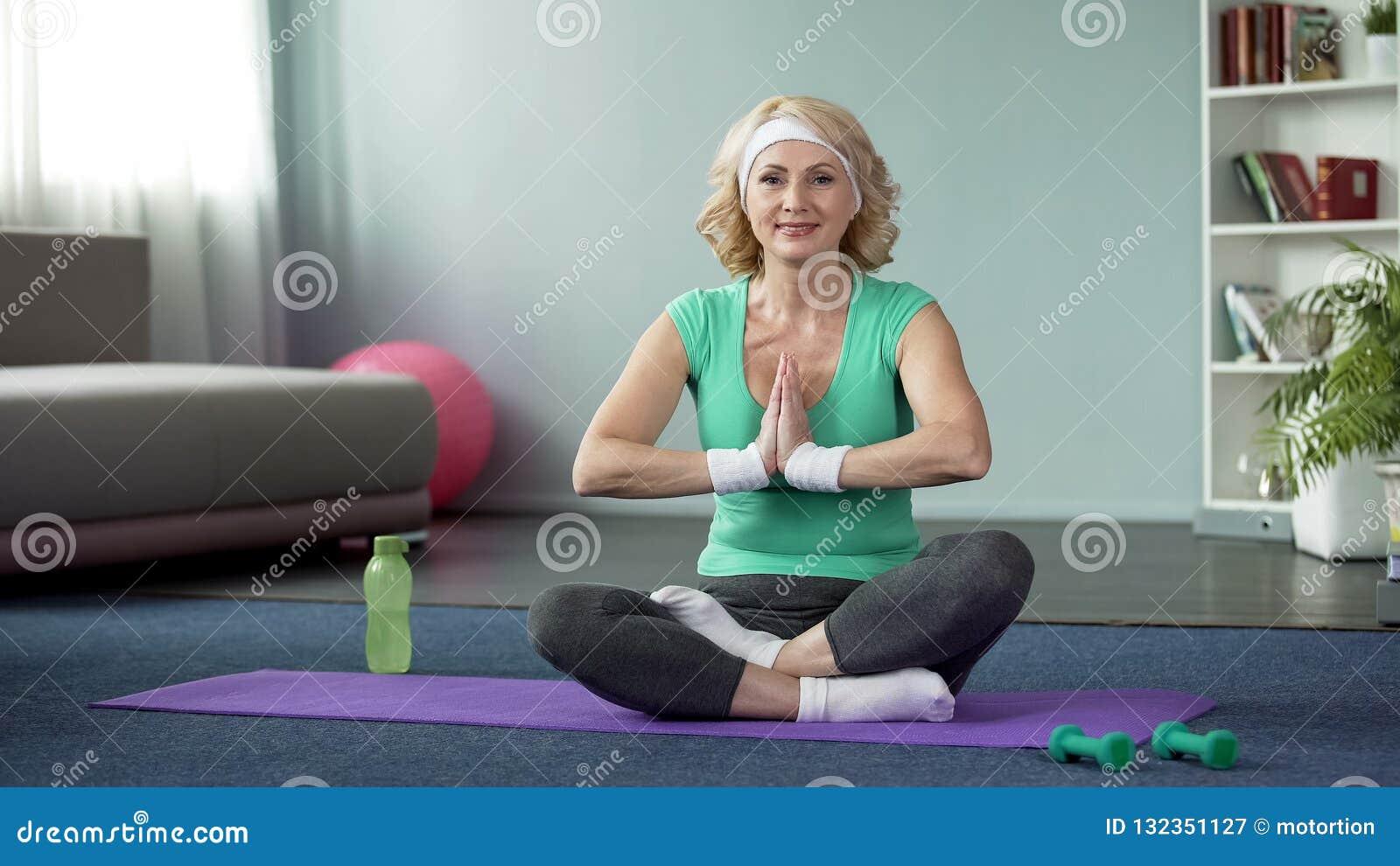 A pose praticando fêmea loura de meia idade dos lótus em casa, fazendo a ioga exercita