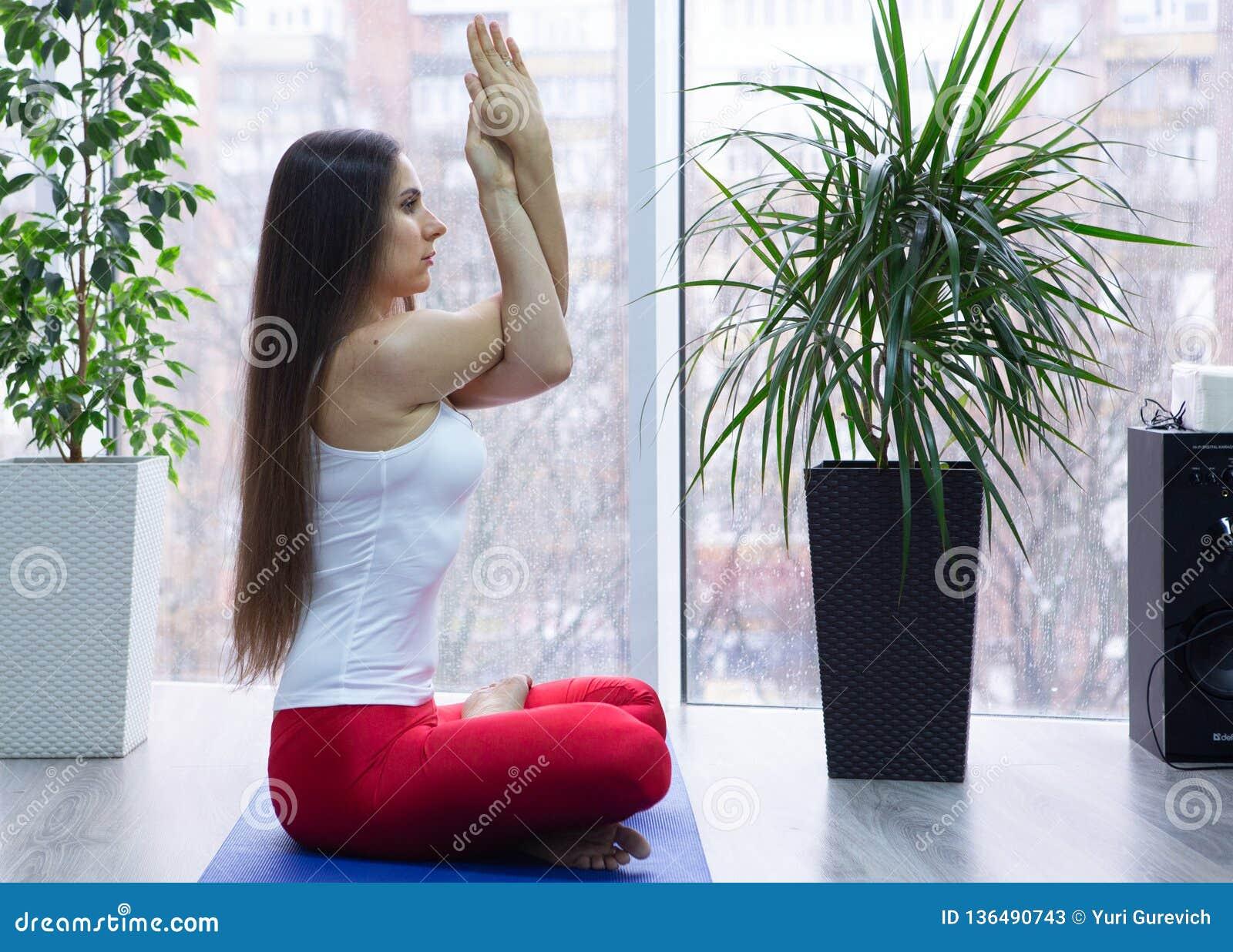 Poserar övande yoga för den unga attraktiva kvinnan som sitter i den Ardha Padmasana övningen, halva Lotus och att utarbeta, den