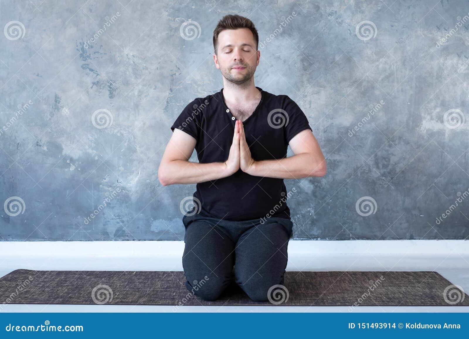 Poserar den övande yogakursen för den unga sportiga mannen som sitter i vajrasana