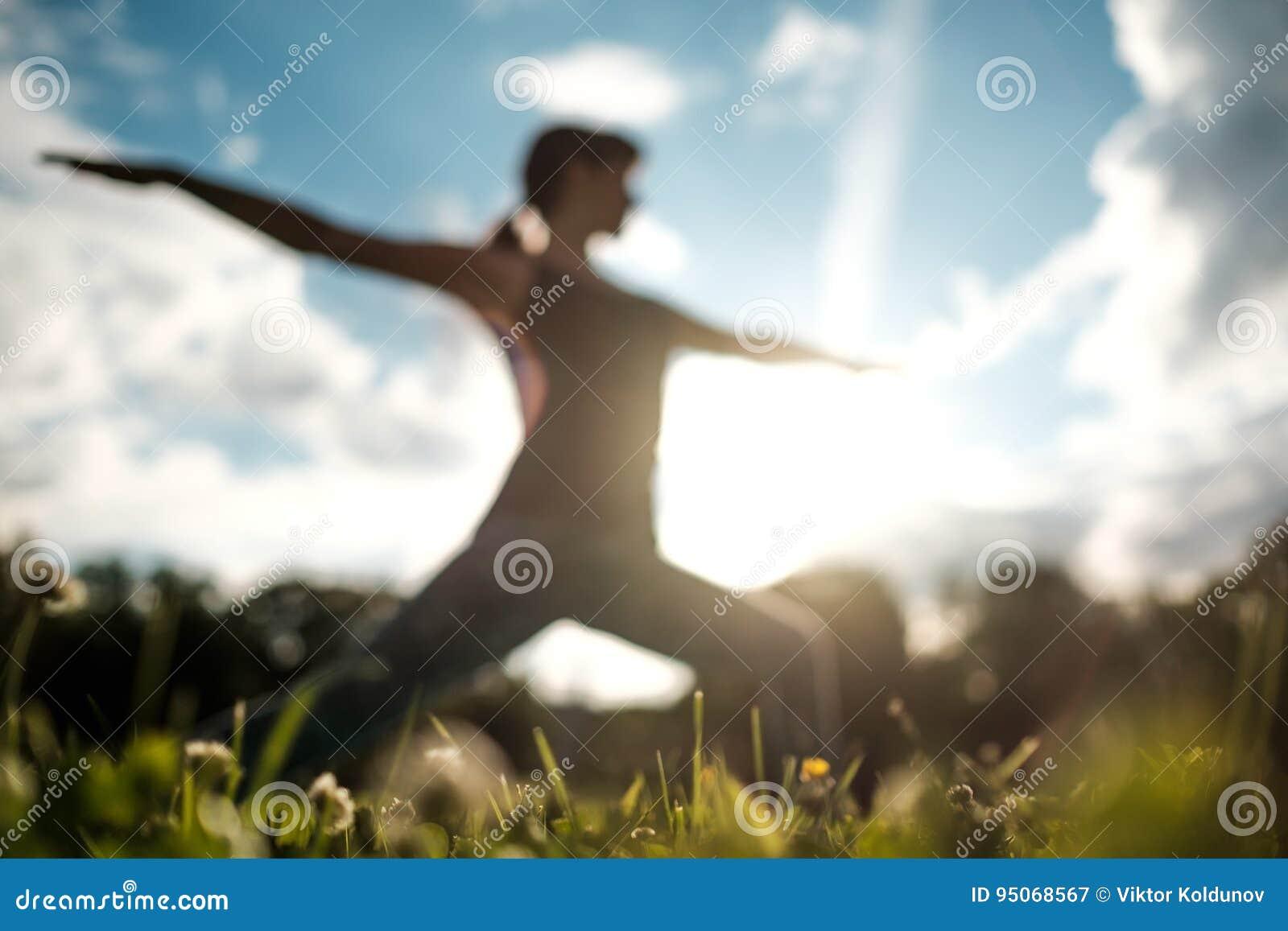 Poserar den caucasian kvinnan för den sportiga passformen som gör den asanaVirabhadrasana 2 krigaren, ställing i natur