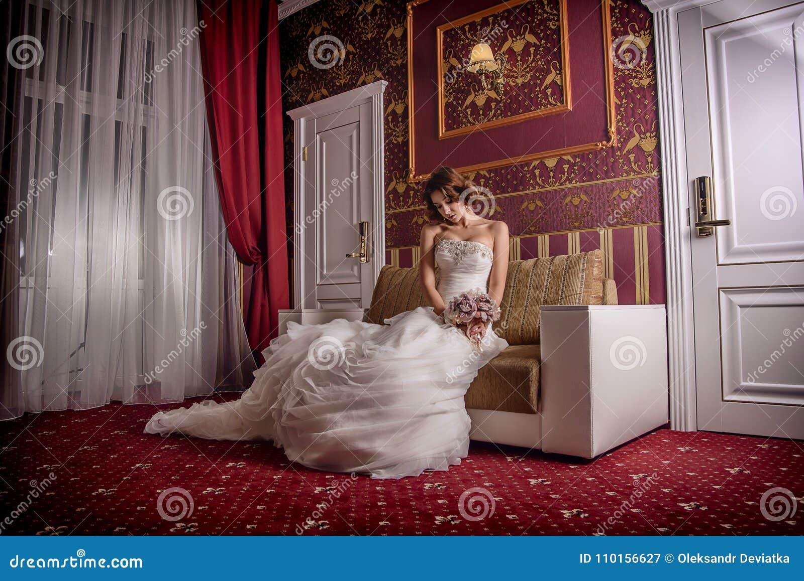 Poserar den härliga bruden för modemodefotoet med lockigt hår i en ursnygg bröllopsklänning med dyrbart perfekt i fantastisk inre