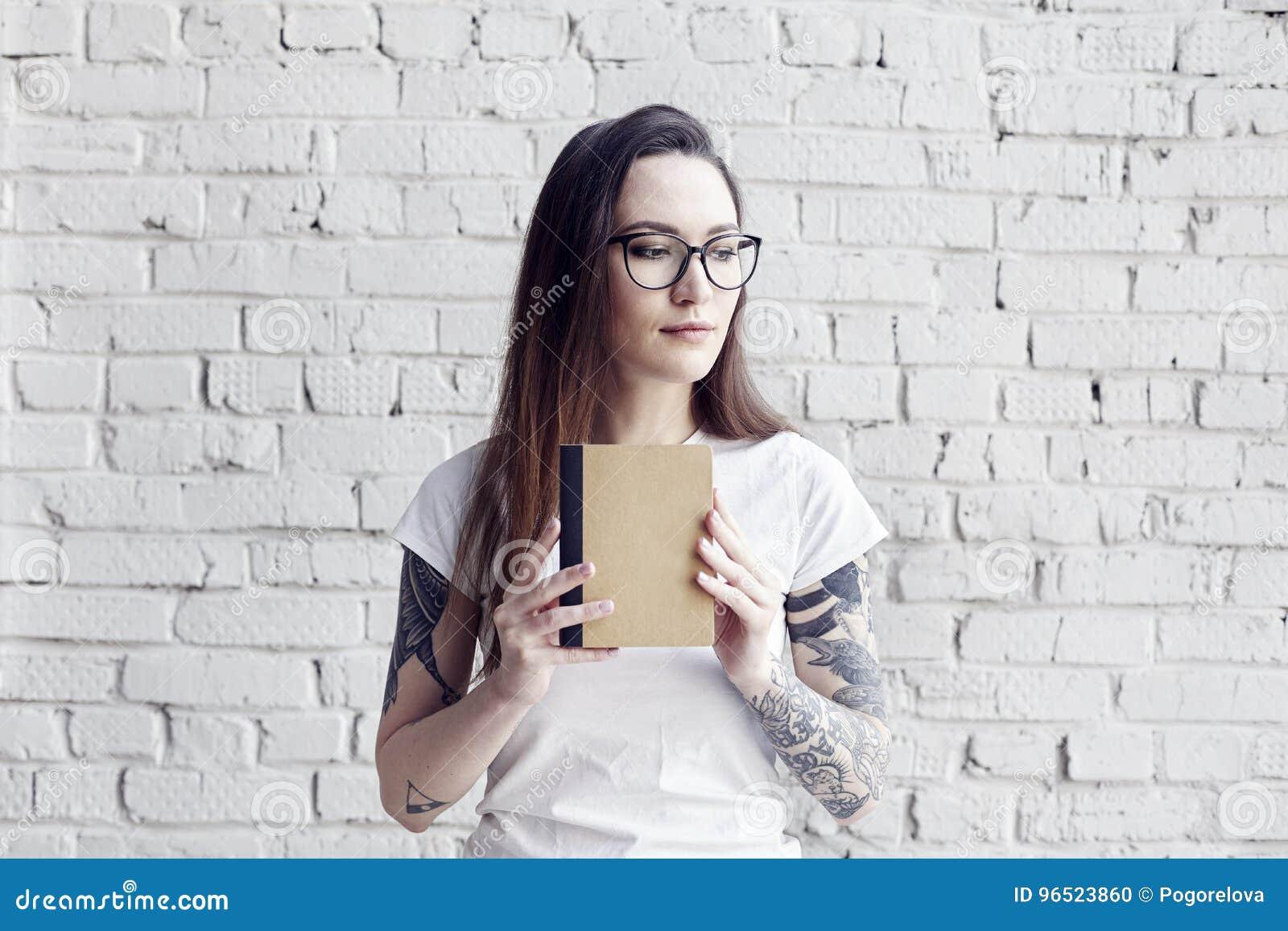 Poserar den nätta hipsteren tatuerade kvinnan i den vita t-skjortan med bok I