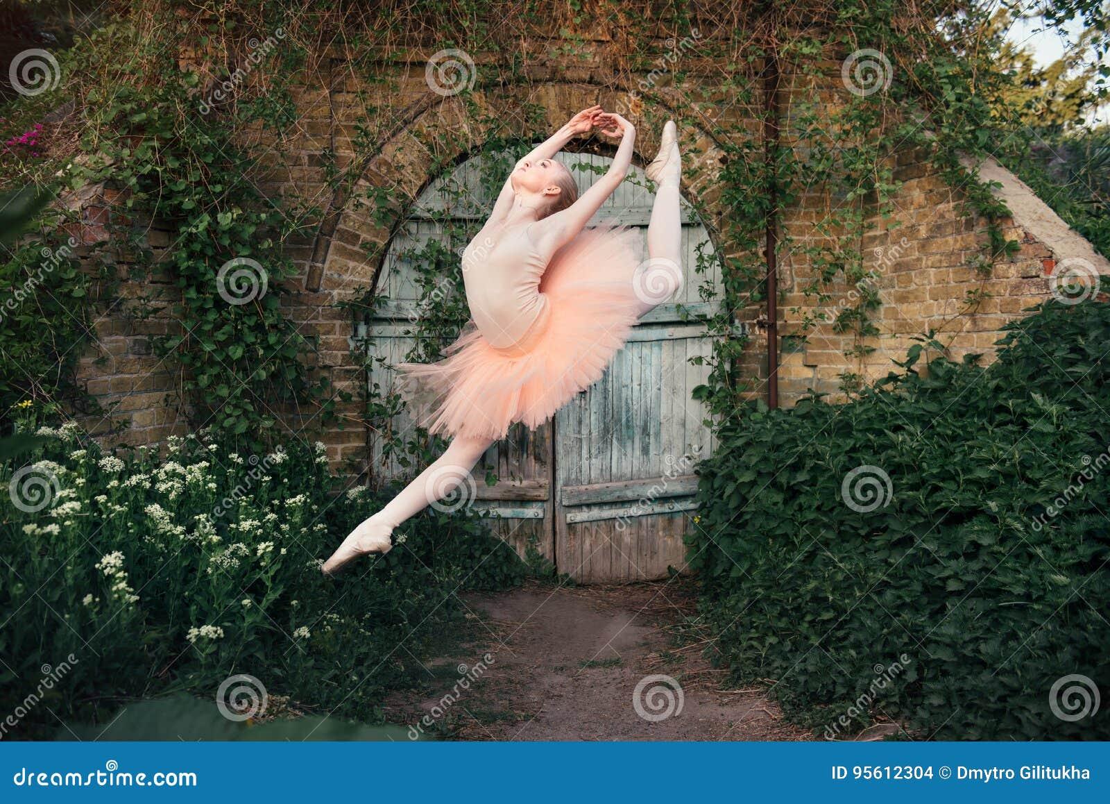 Poserar klassisk balett för ballerinadansen utomhus i stads- backgro
