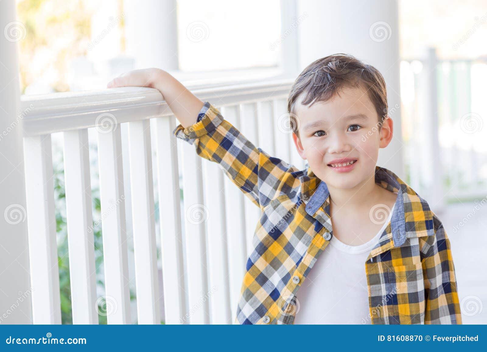 Poses novas adoráveis do menino da raça misturada em seu Front Porch