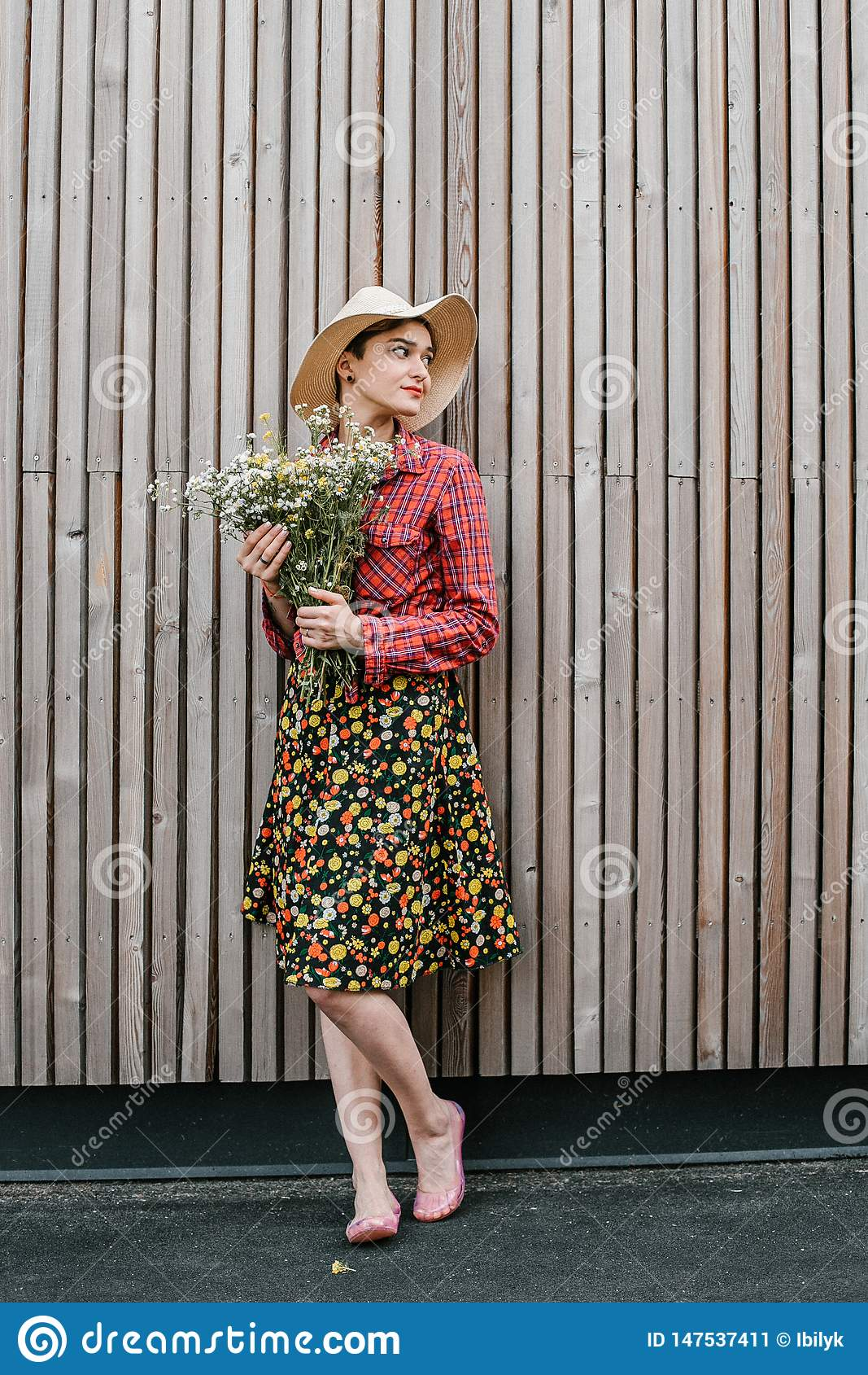 Posição à moda da menina com flores Mulher bonita perto de uma parede de madeira Estilo da mola Caminhada do ver?o Humor rom?ntic