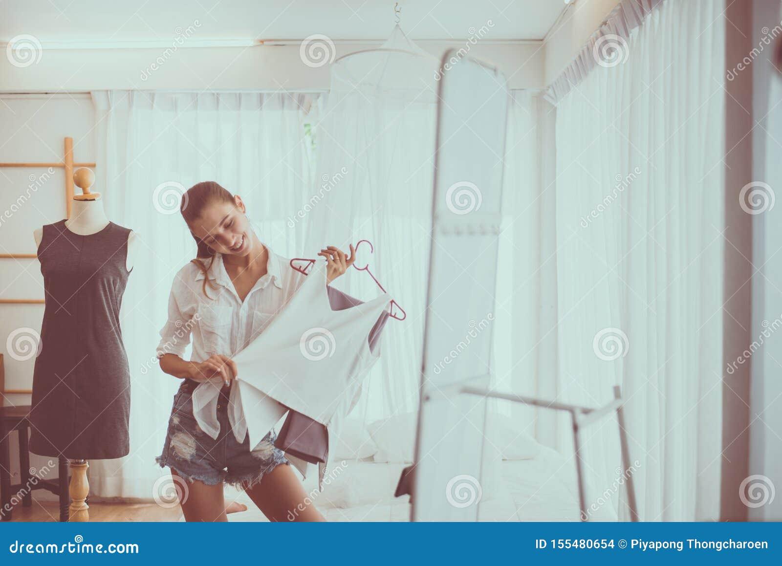 Posição bonita nova da mulher na loja de roupa e no conceito nos vestidos da escolha, feliz e no sorriso, da forma e do estilo de