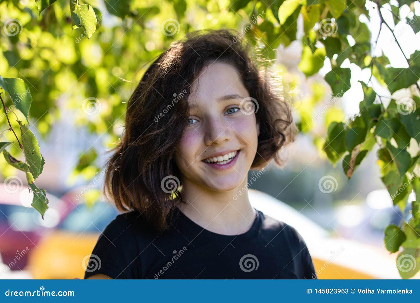 Posi??o bonito da menina do jovem adolescente sob uma ?rvore de Linden cercada pelas folhas