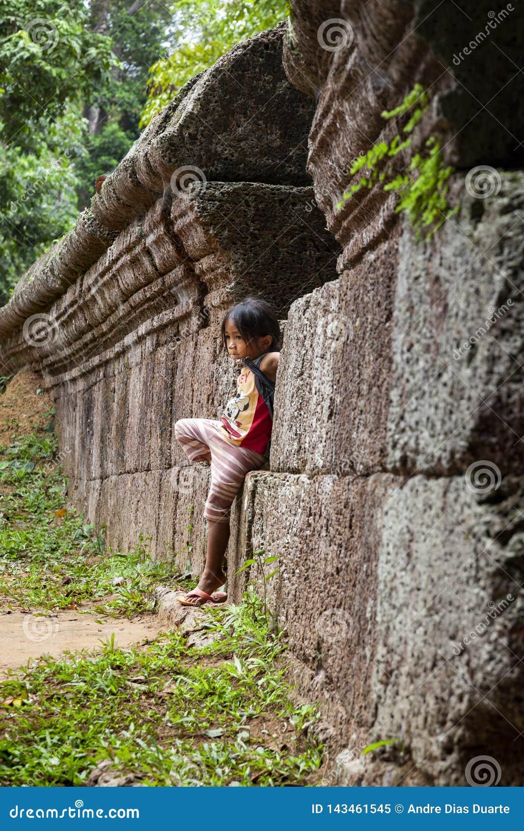 Posição da menina contra uma parede de pedra velha