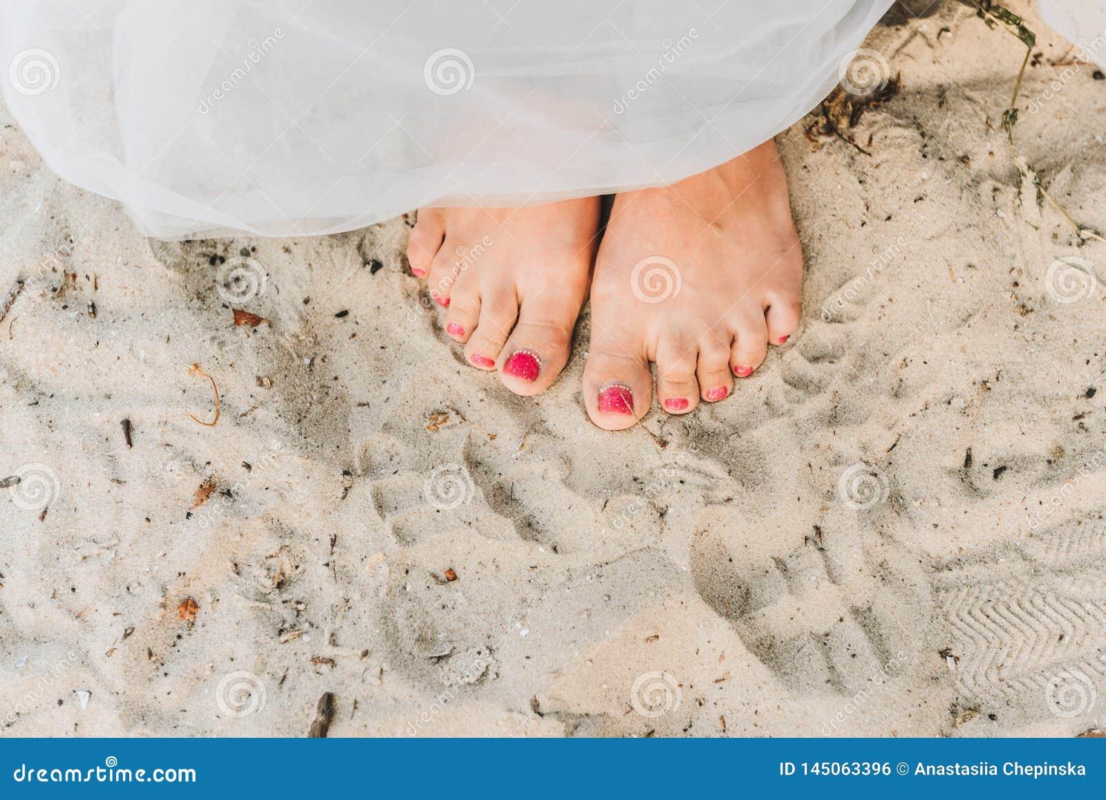 Posição da mulher descalça em uma praia