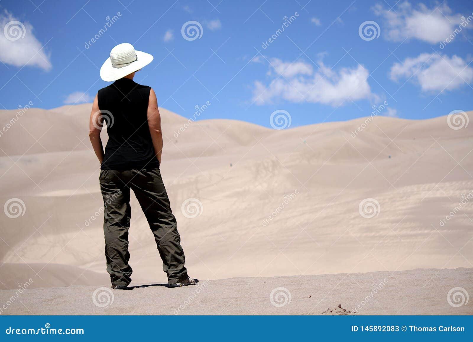 Posição da mulher em dunas de areia do deserto