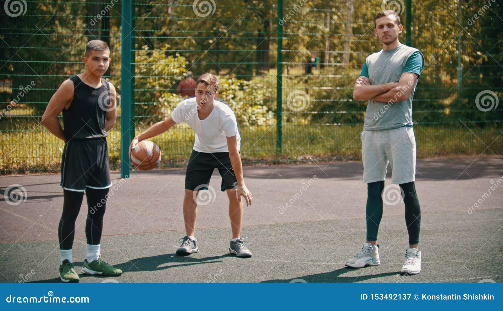 Posição de três sportsmens no ar livre do campo de básquete e vista na câmera - um deles que jogam com uma bola
