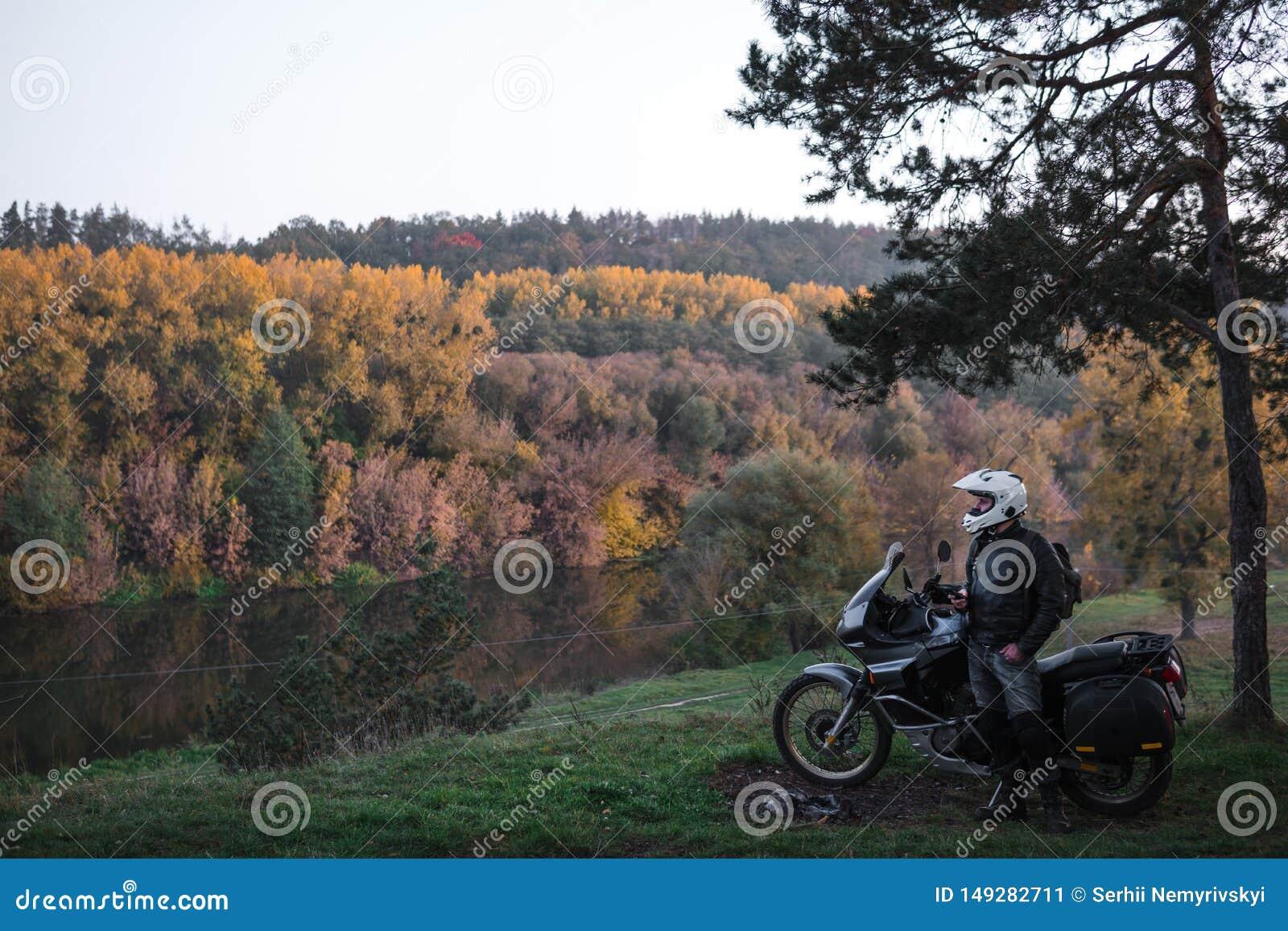 A posi??o do cavaleiro com motocicleta da aventura, engrenagem do motociclista, um motorista do velomotor olha, conceito do estil