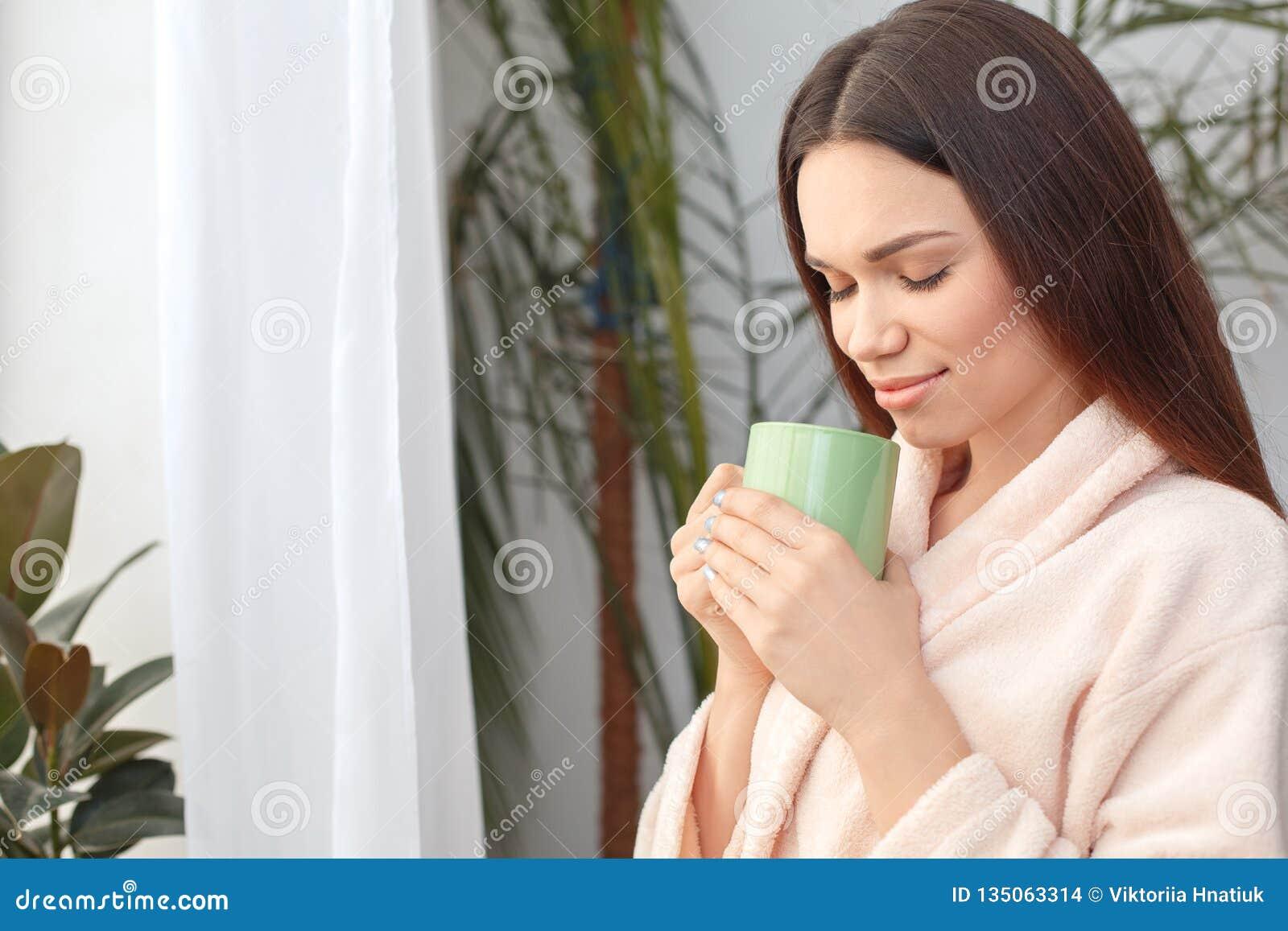 A posição do cuidado da beleza da jovem mulher em casa que bebe o chá quente fechou os olhos relaxados