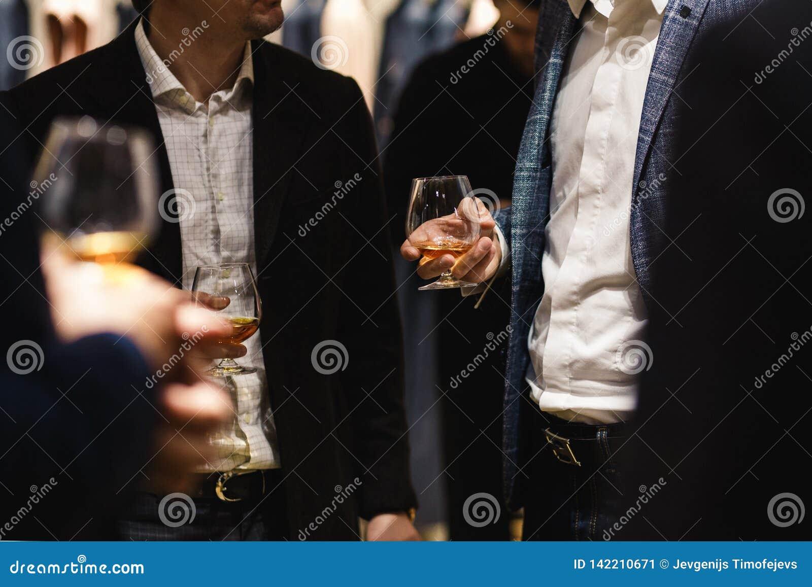 Posição dos povos que conversa em um jantar de negócio que guarda o gosto do vidro do uísque e de vinho e que degustating o alime