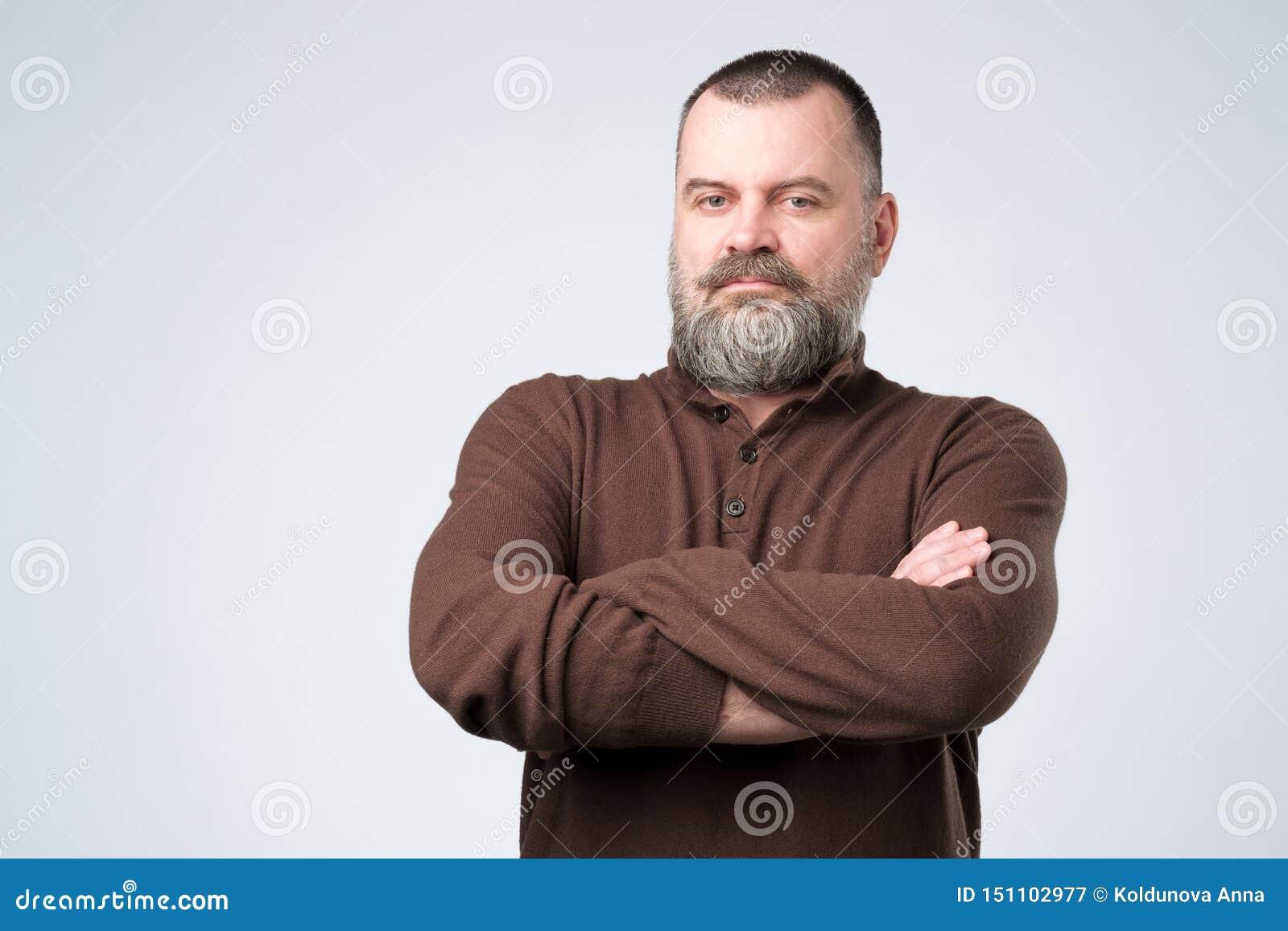 Posição europeia madura séria do homem com os braços dobrados