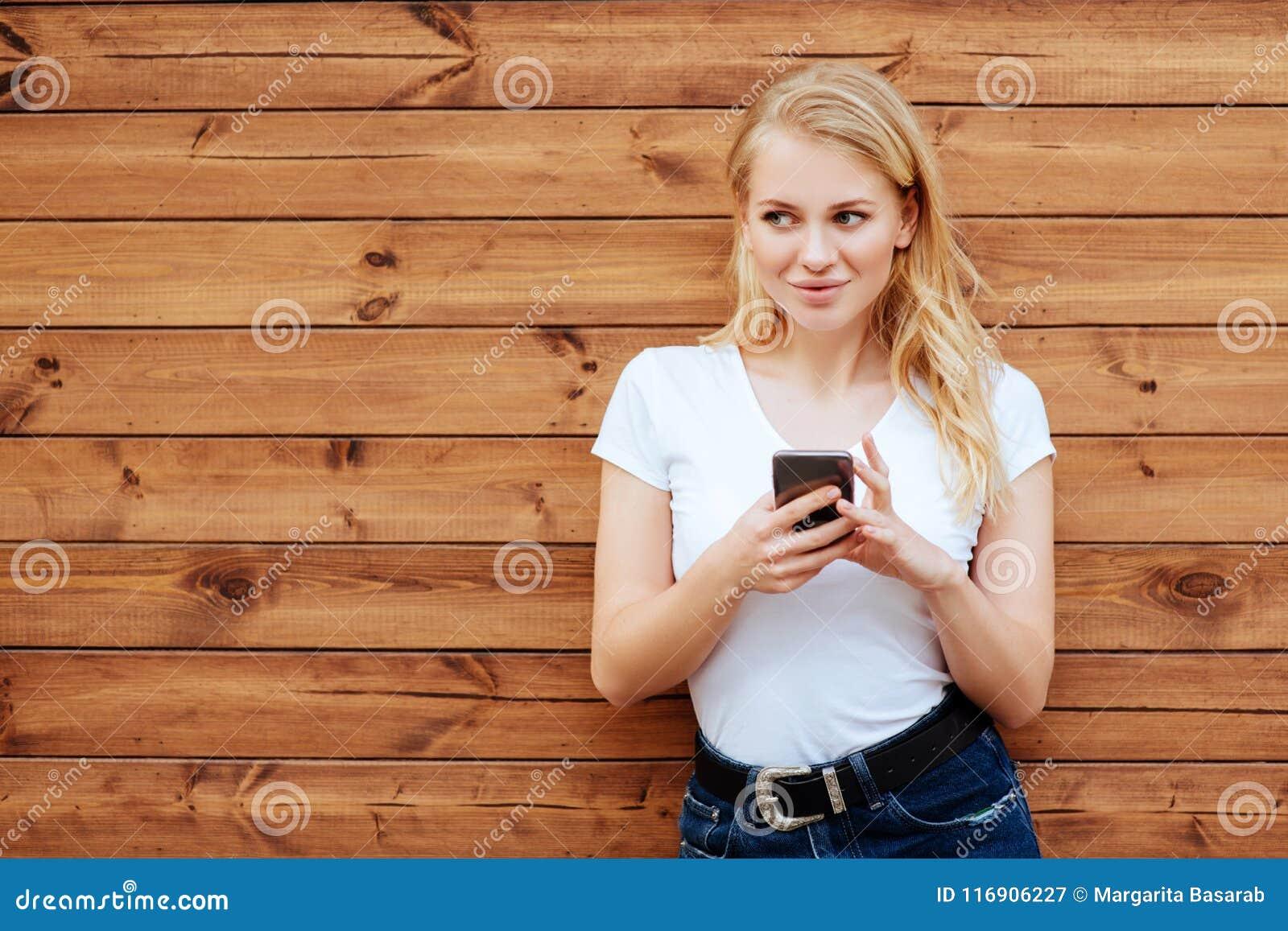 Posição fêmea de riso atrativa com telefone celular contra o fundo de madeira da parede