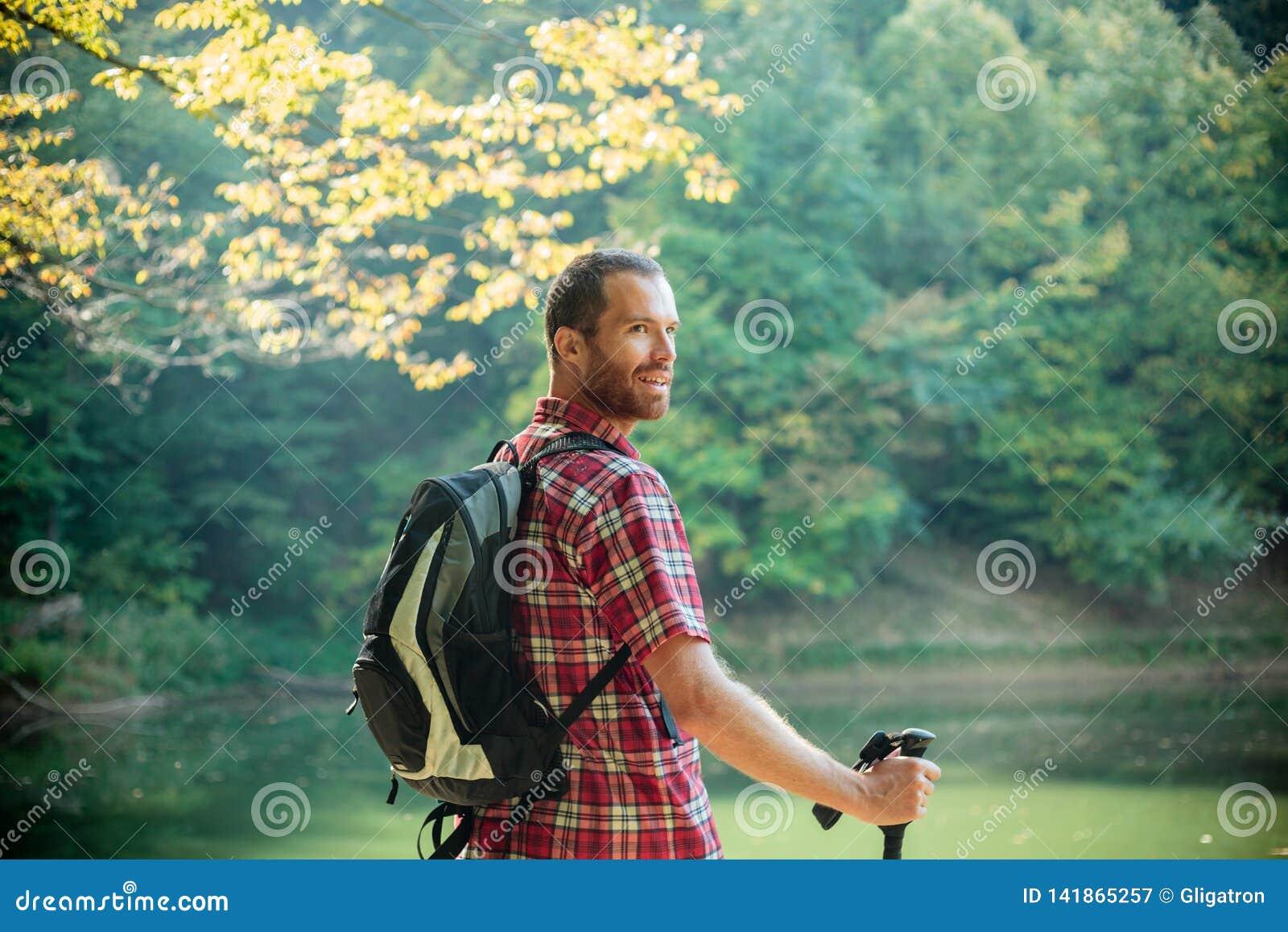 Posição feliz do homem novo pelo lago da montanha cercado pela floresta verde luxúria que olha sobre seu ombro