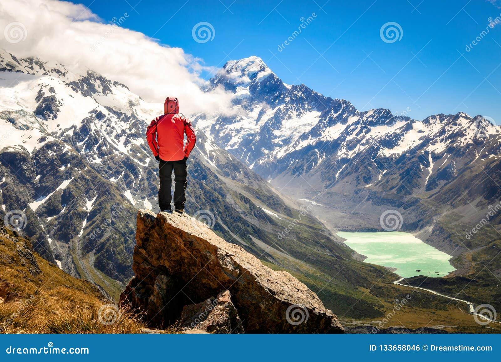 Posição livre feliz do homem do turista estendido acima de olhar a paisagem da cabana de Mueller, TA do rio e das montanhas Cozin