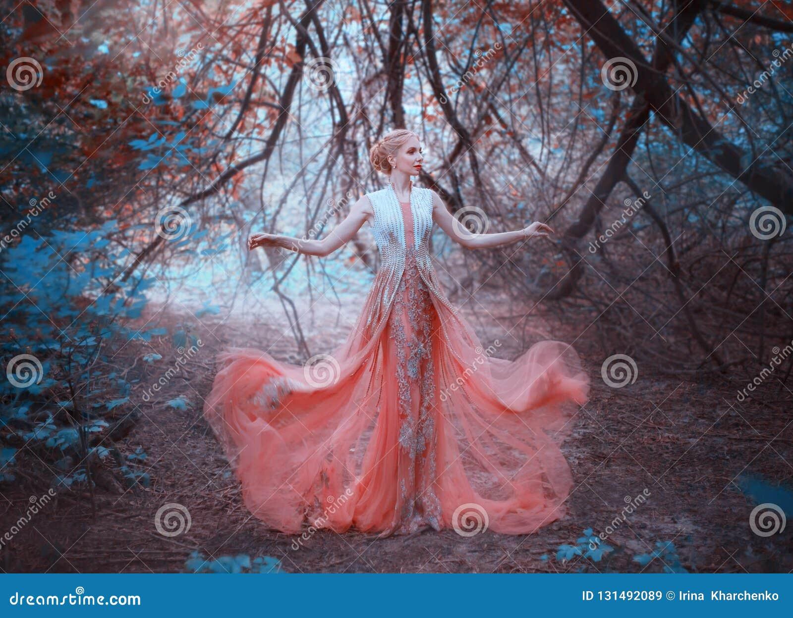 Posição loura do duende da rainha deliciosa na floresta perto dos ramos das árvores que tocam na terra, vestindo uma luz
