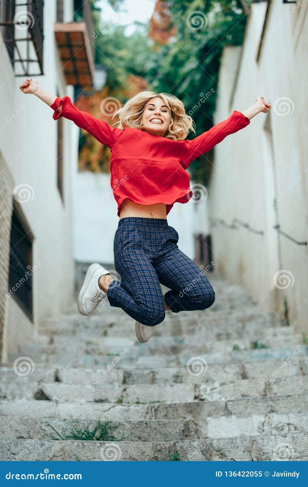 Posição loura nova feliz da mulher em etapas bonitas na rua