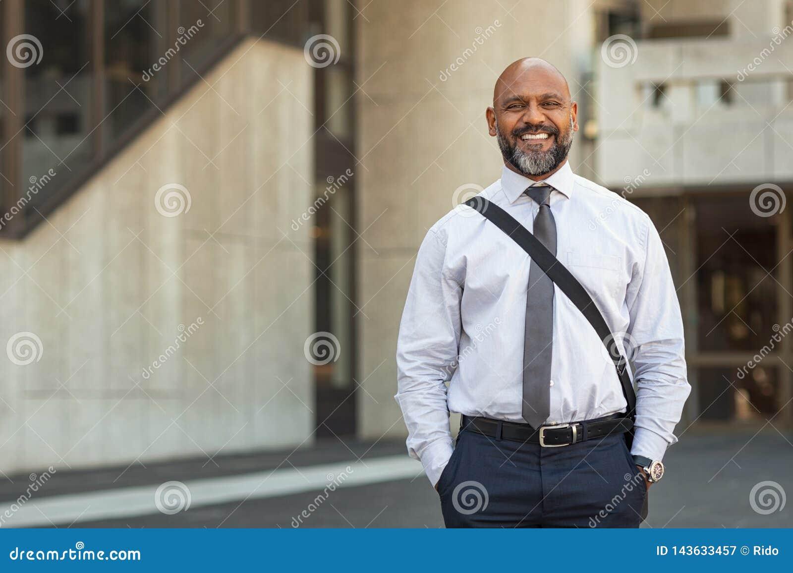 Posição madura feliz do homem de negócios na rua