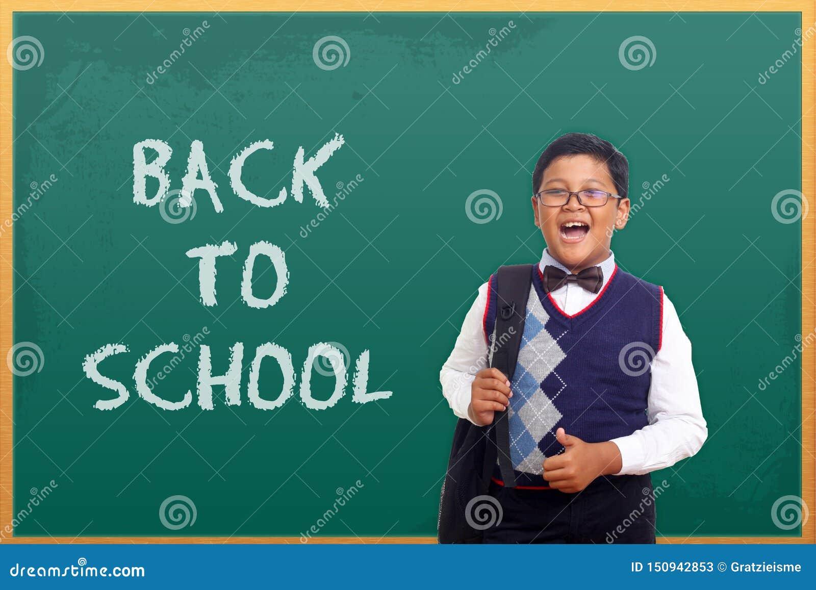 A posição masculina do estudante da escola primária na classe ao vestir o uniforme e leva o saco com garatujas, comemora de volta