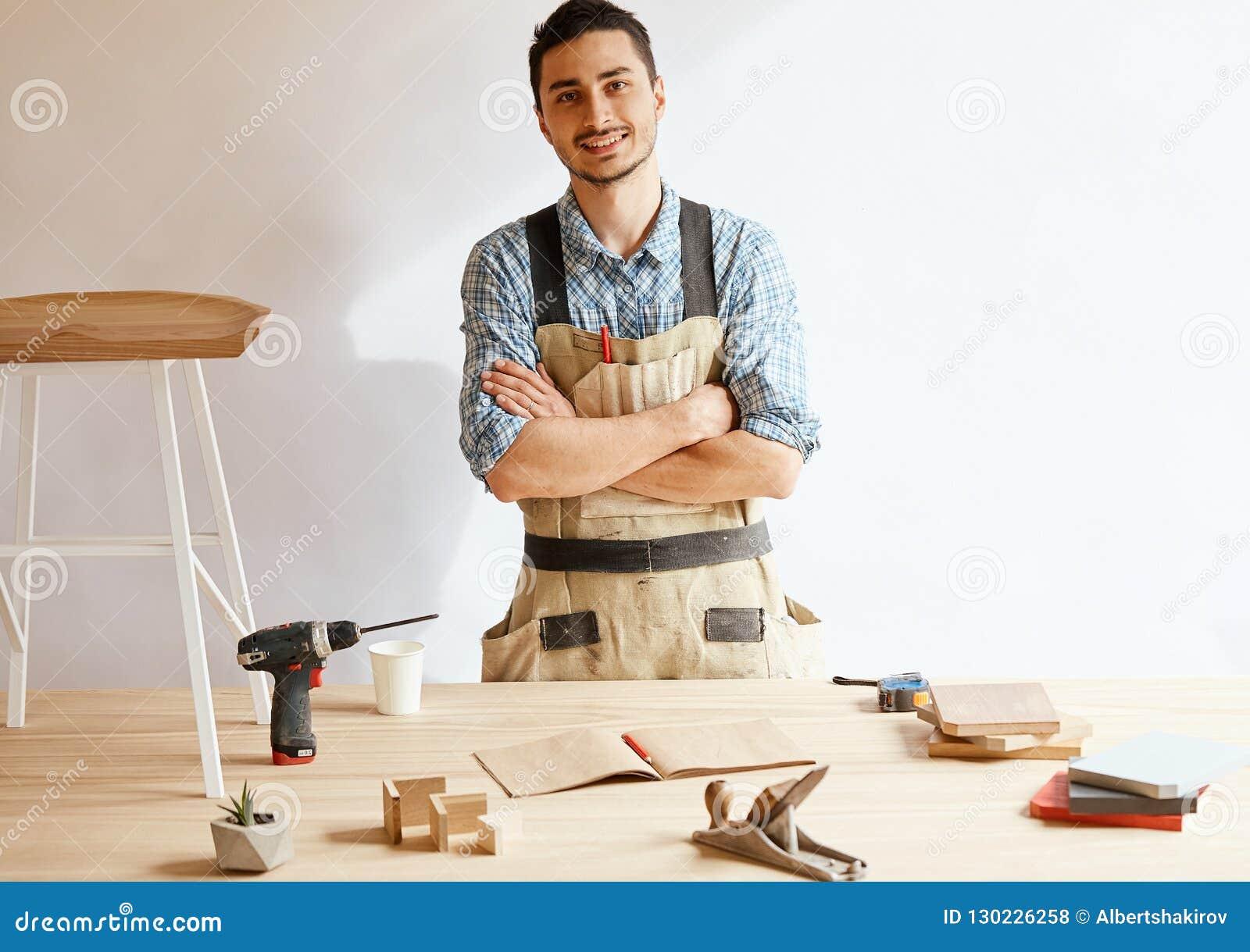 Posição nova segura do carpinteiro ao lado da bancada em sua oficina da carpintaria
