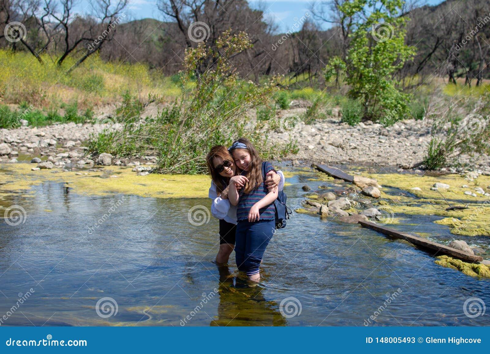 Posi??o da mulher e da filha e tother de riso ao jogar em um c?rrego ou em um rio