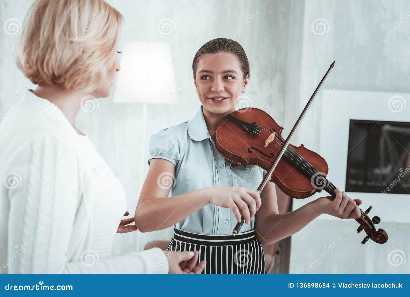 Positief aardig meisje die haar muziekleraar bekijken