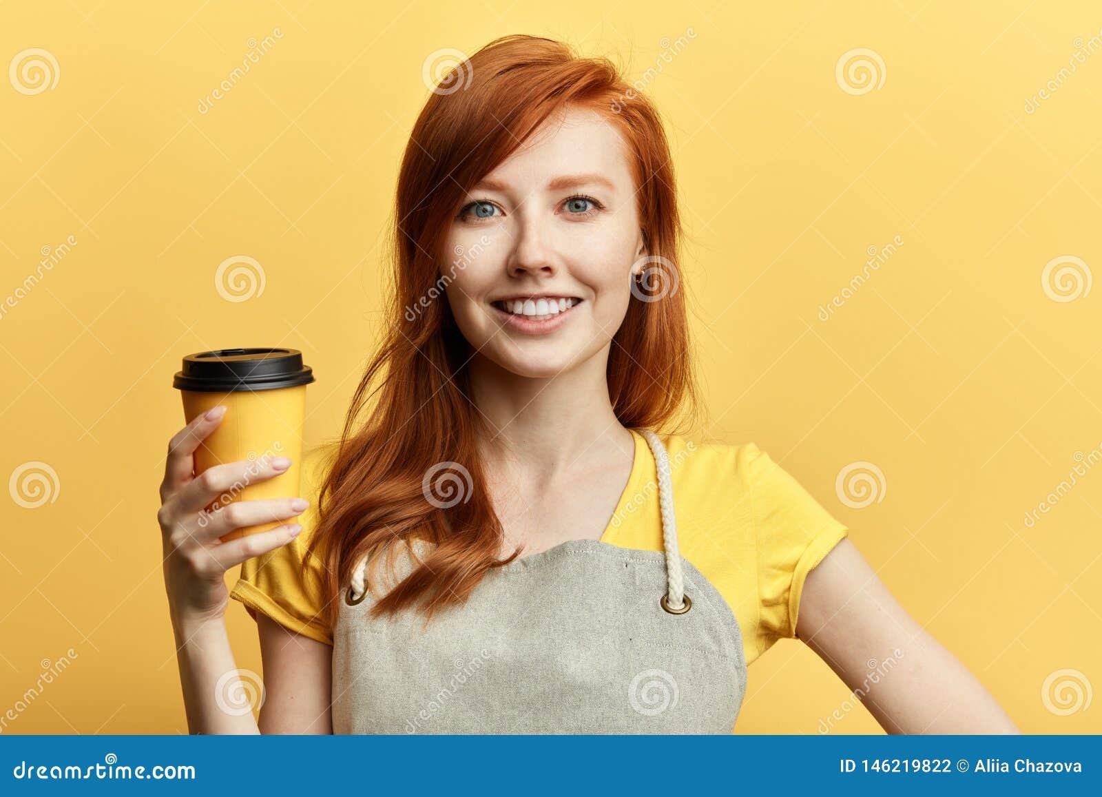 Positief schitterend meisje die een kop van koffie aanbieden