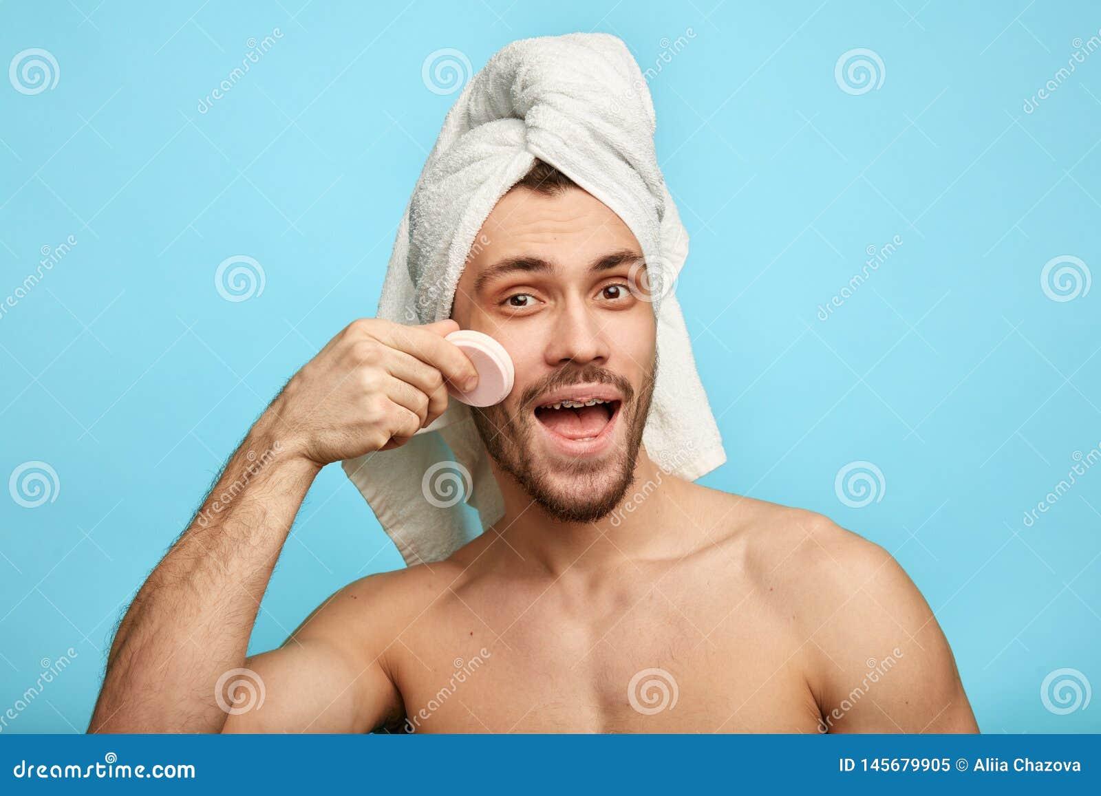 Positieve gelukkige mens die poeder op zijn gezicht toepassen