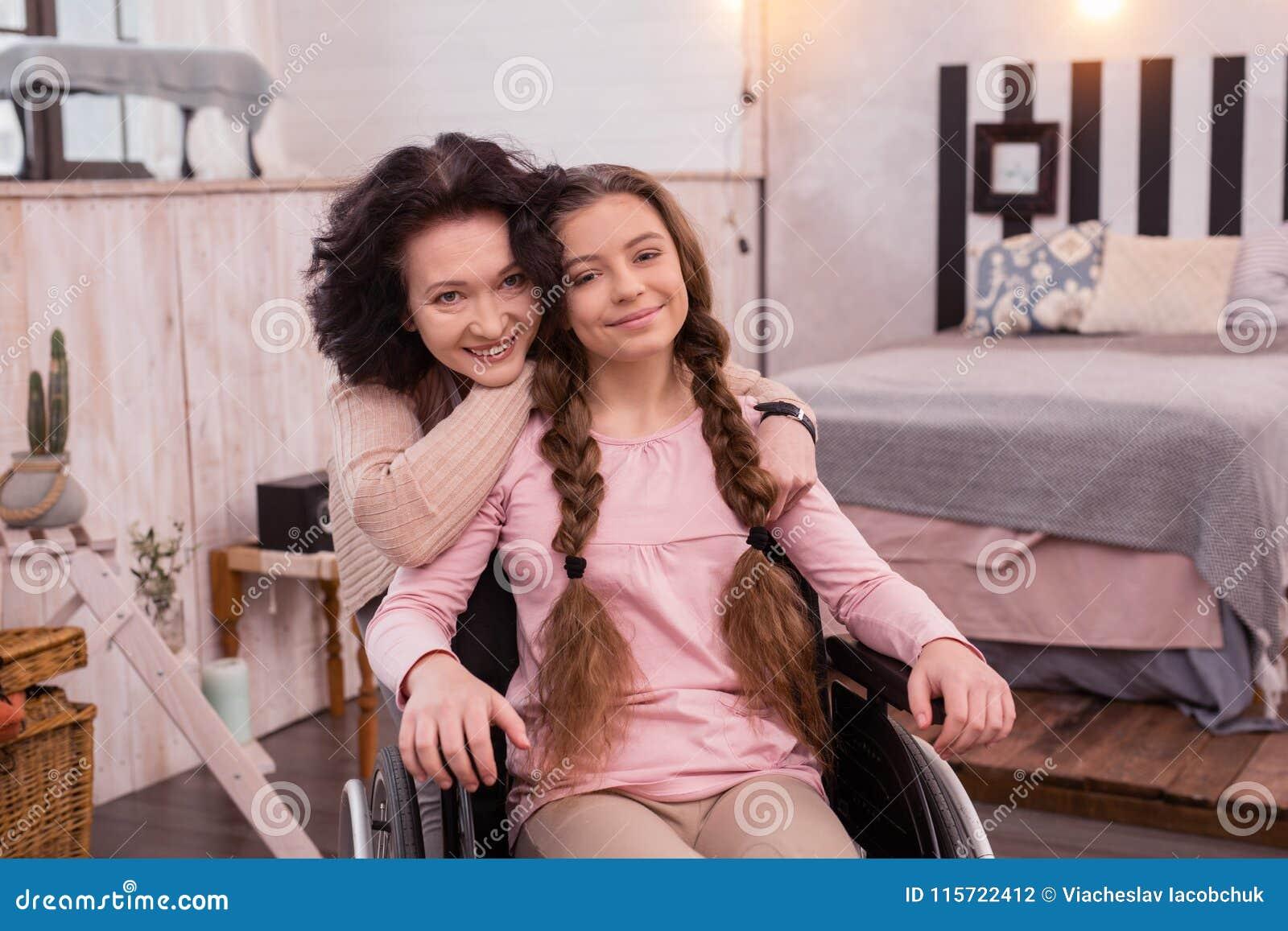 Positieve vrouw die gehandicapt meisje koesteren