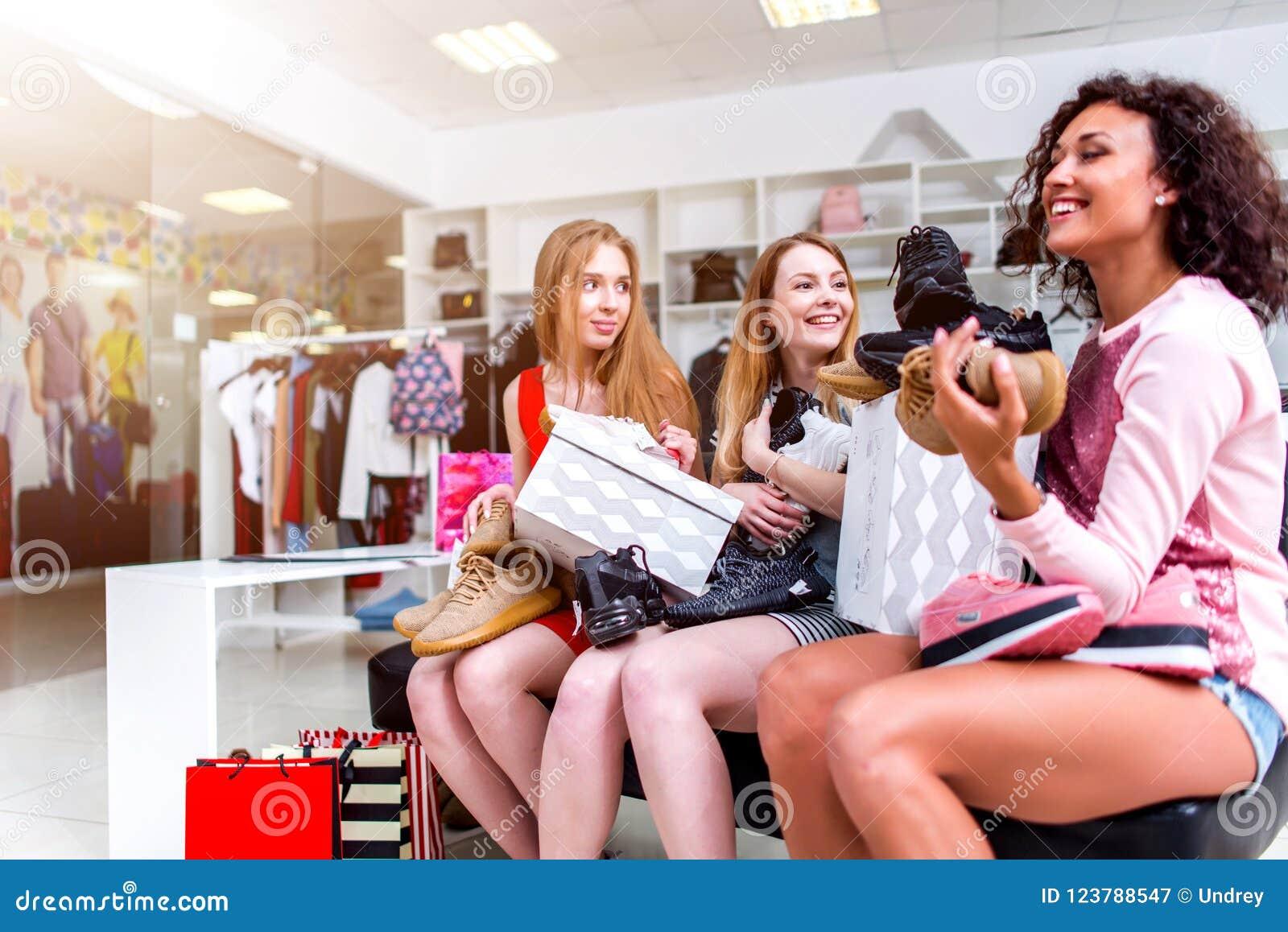 Positieve vrouwelijke vrienden gelukkig met nieuwe zitting met nieuwe schoenen en dozen op hun overlapping in klerenopslag