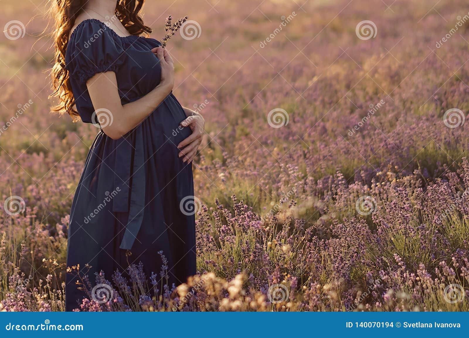 Position aux cheveux longs de femme enceinte un jour ensoleillé dans un domaine de lavande avec un bouquet de lavande