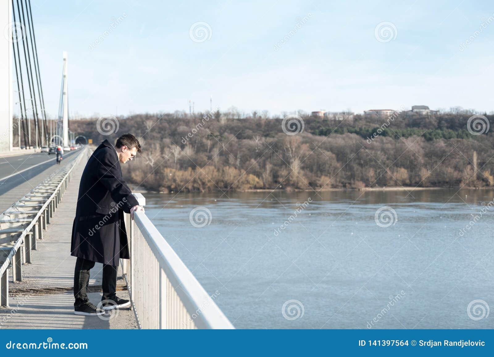 Position déprimée et soucieuse isolée d homme sur le pont avec des pensées suicidaires déçues dans les personnes regardant vers l